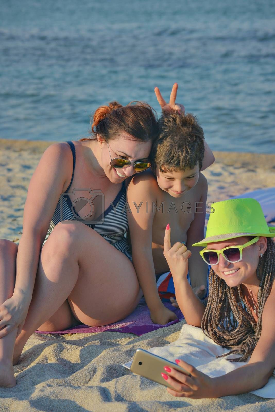 A group of three - two females and a kid are making funny rabbit ears selfie on a quiet beach.