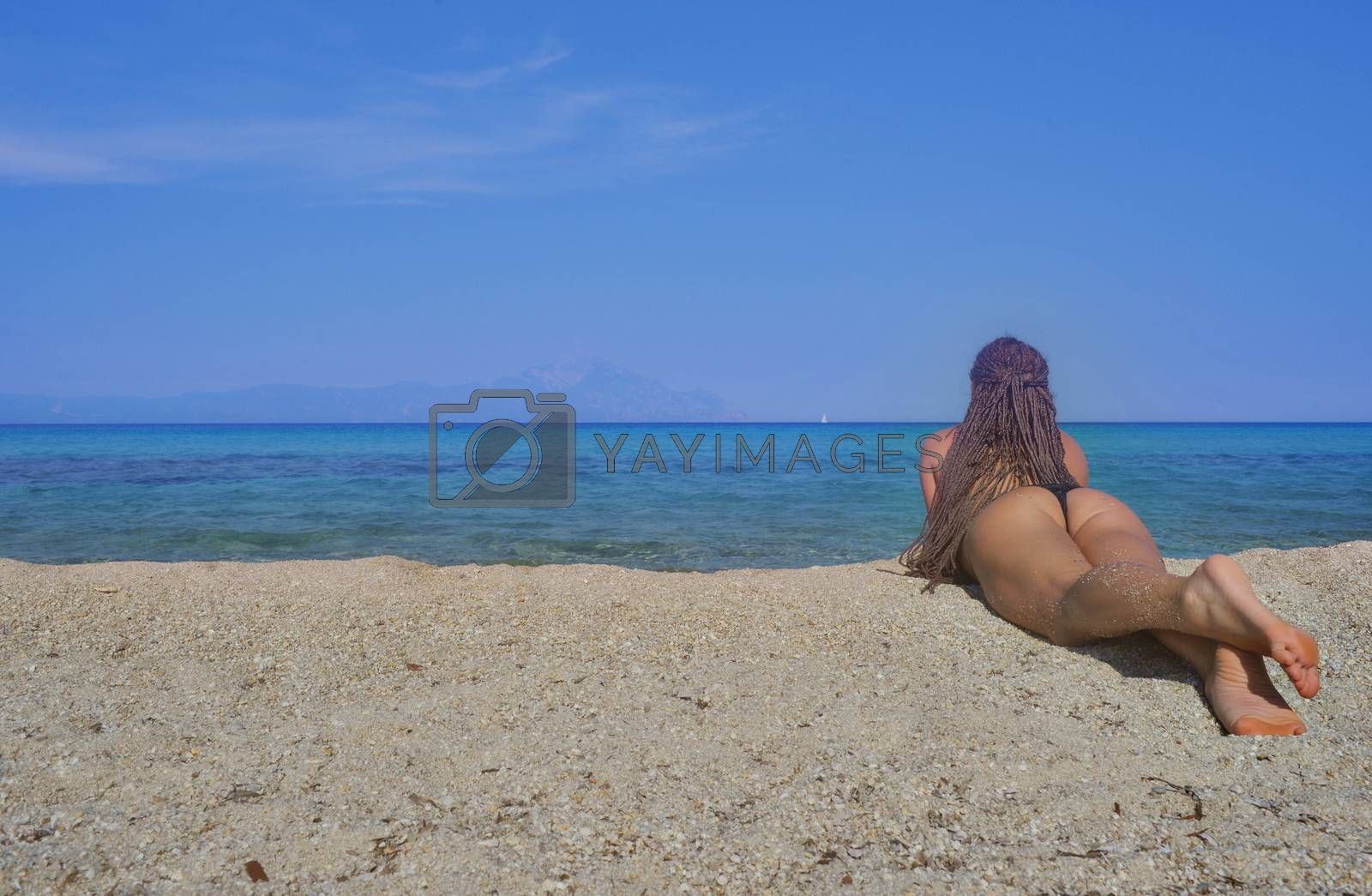 Girl with beautiful body with bikini is lying on the beach looking at sea.
