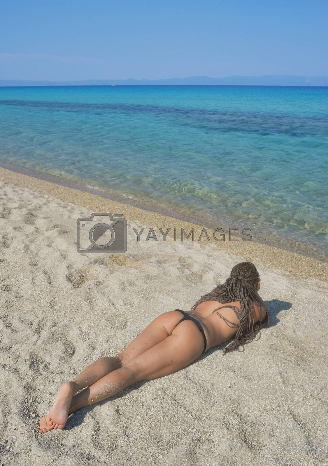 Girl with beautiful body with bikini is lying on the beach.
