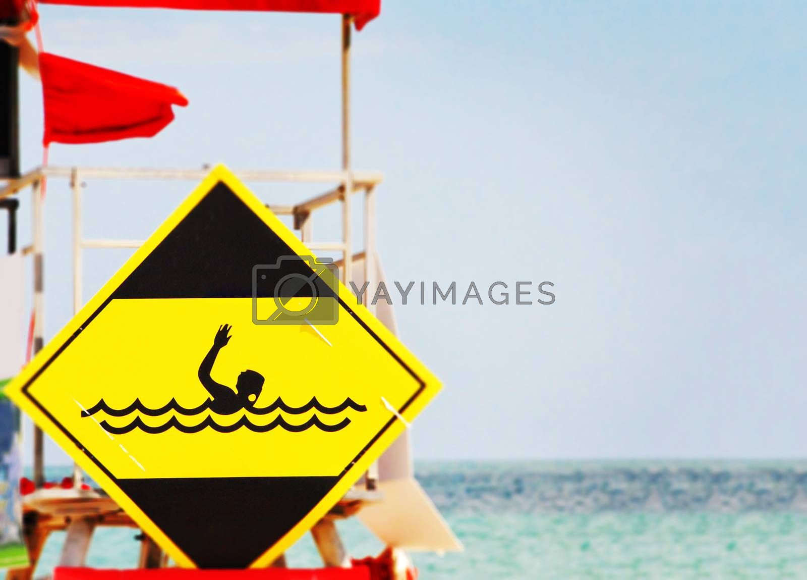 yellow danger signal depicting a drowning swimmer in the waves of a rough sea