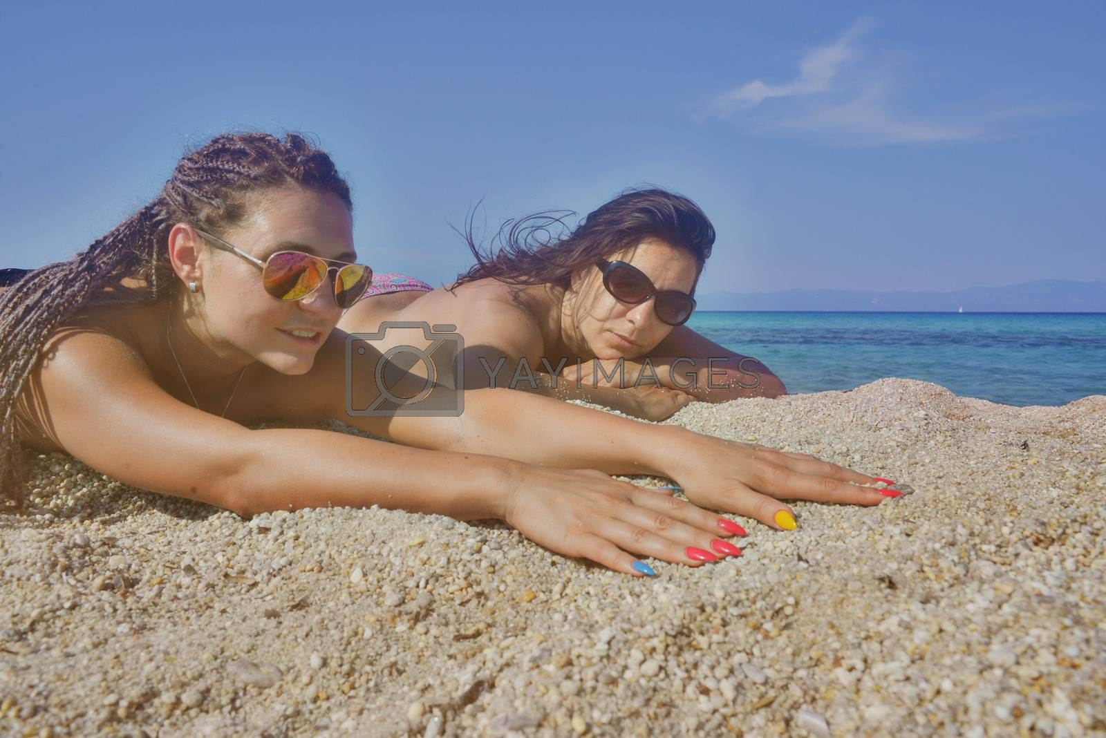 Two beautiful girls on a distant sea shore lying on the sand.