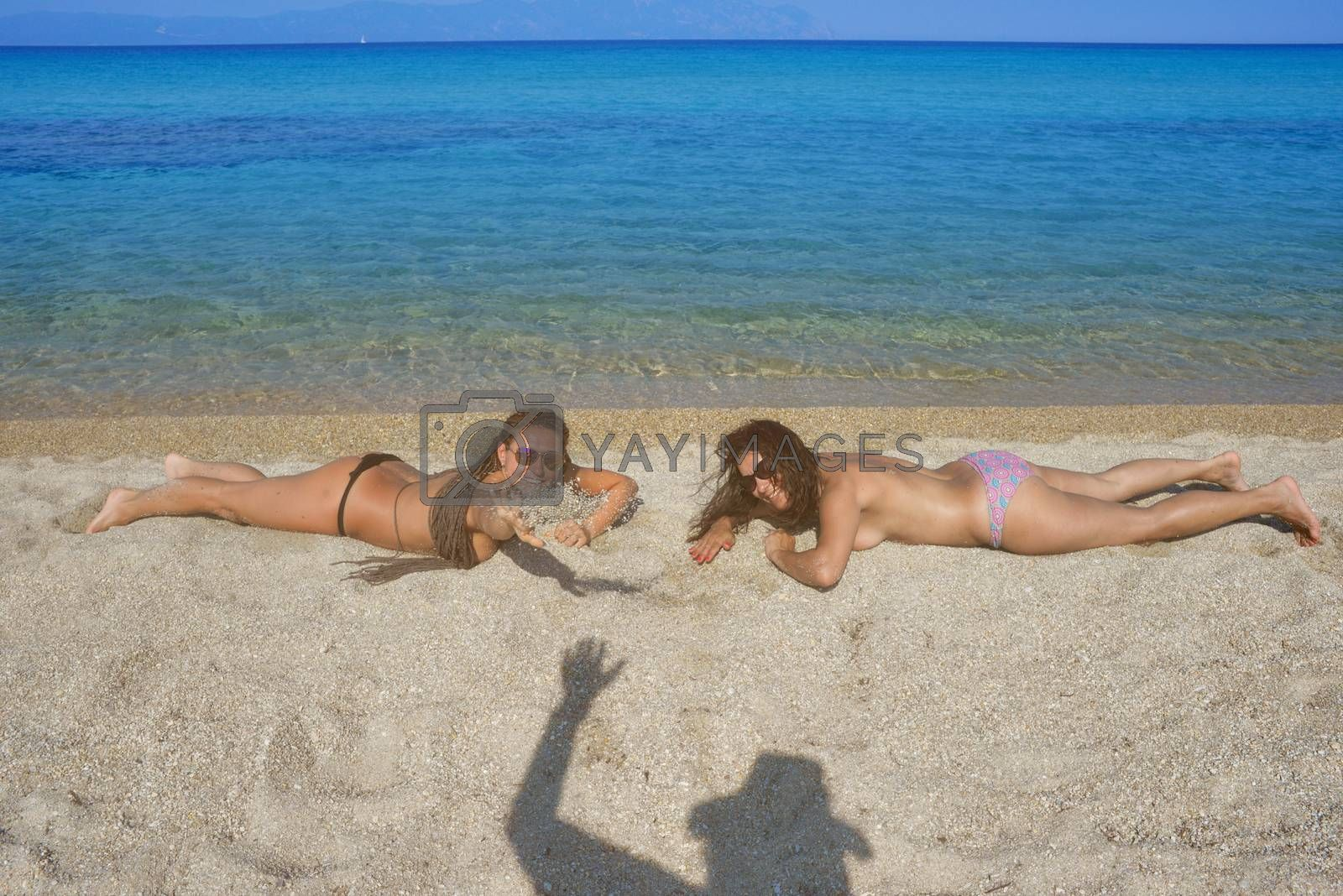 Two beautiful women on the beach are smiling to a person, shown with his waving shadow on the sand.