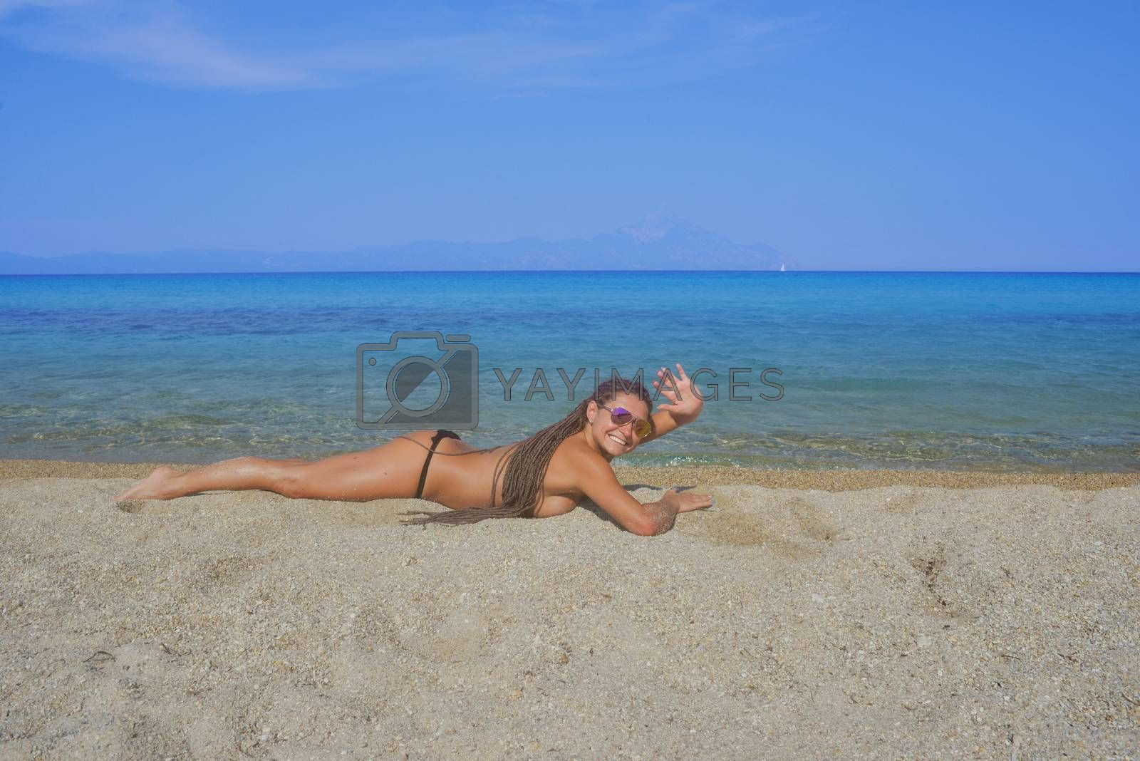A beautiful woman with bikini on a quiet distant sand beach waving to camera.