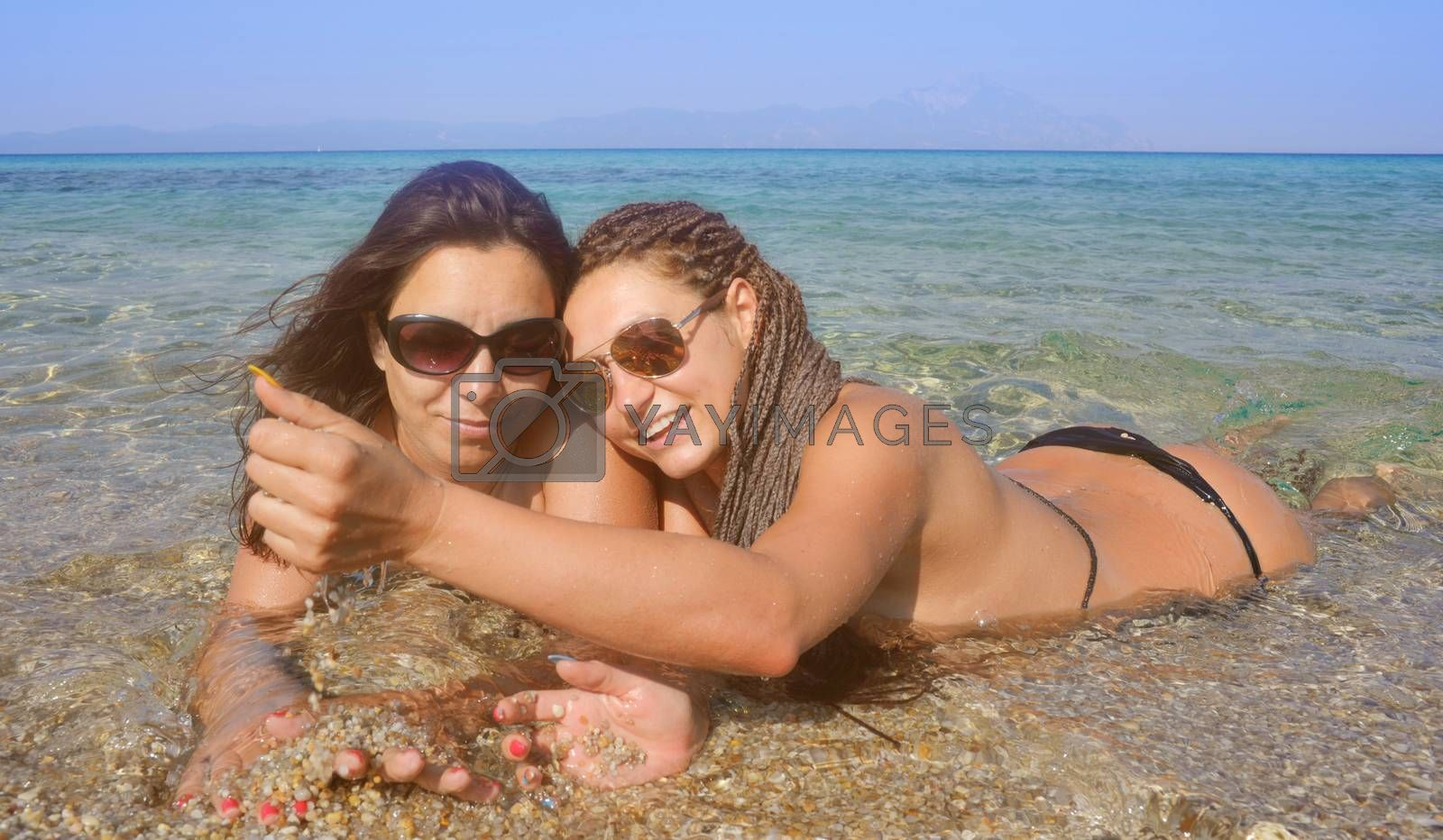 Two beautiful girls on a distant sea shore lying in the water playing with sand.