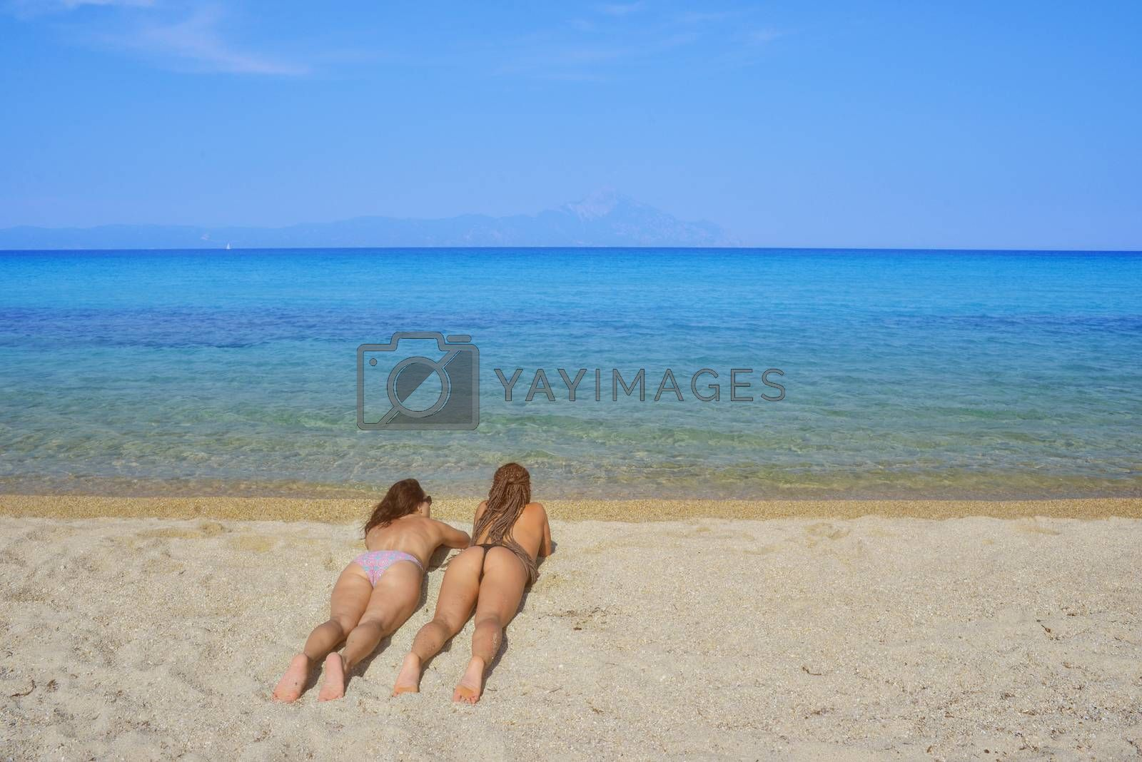 Two beautiful females in bikini lying on a sandy beach over a calm sea.