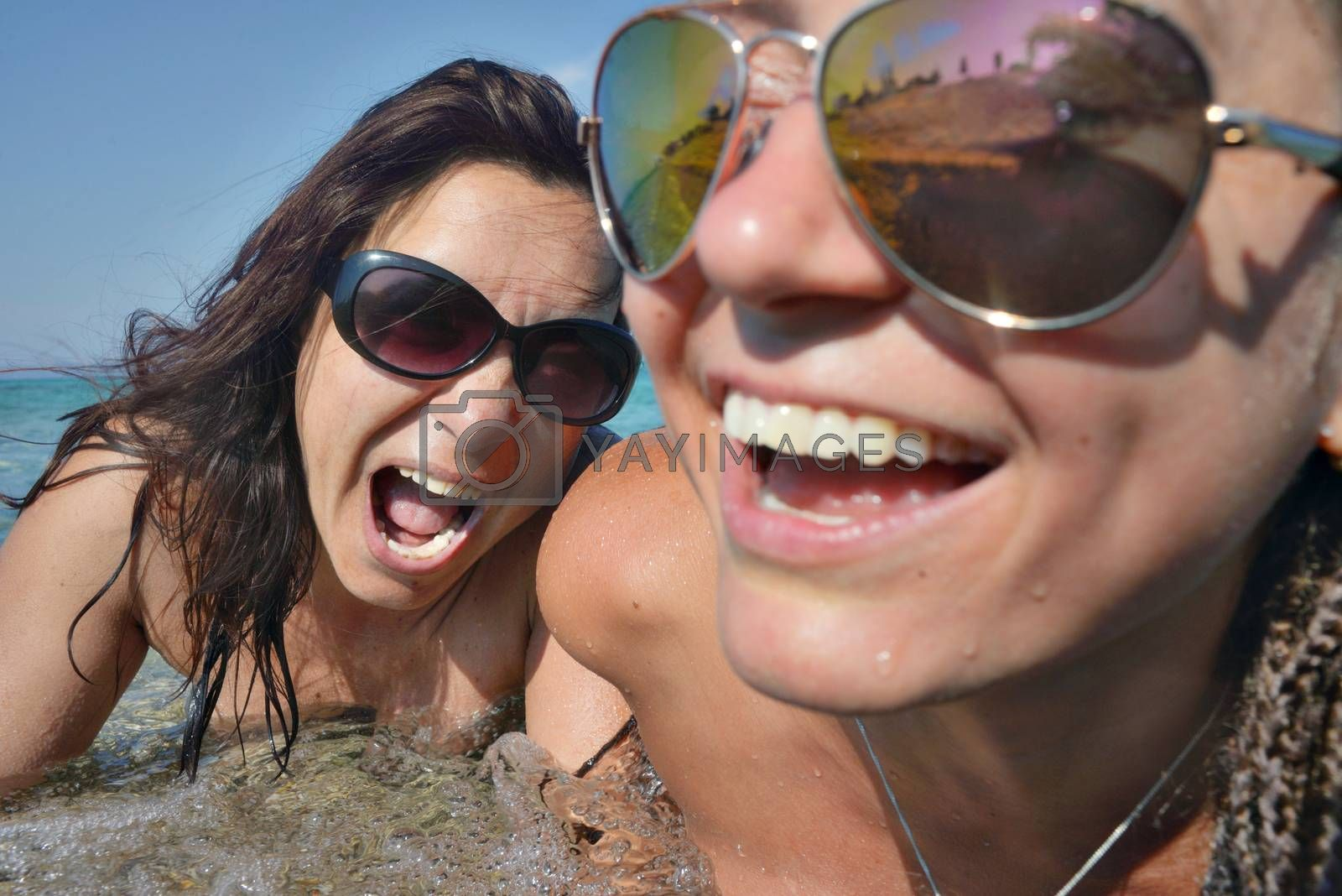 Two female faces - one smiling out of focus and one screaming in sea water.