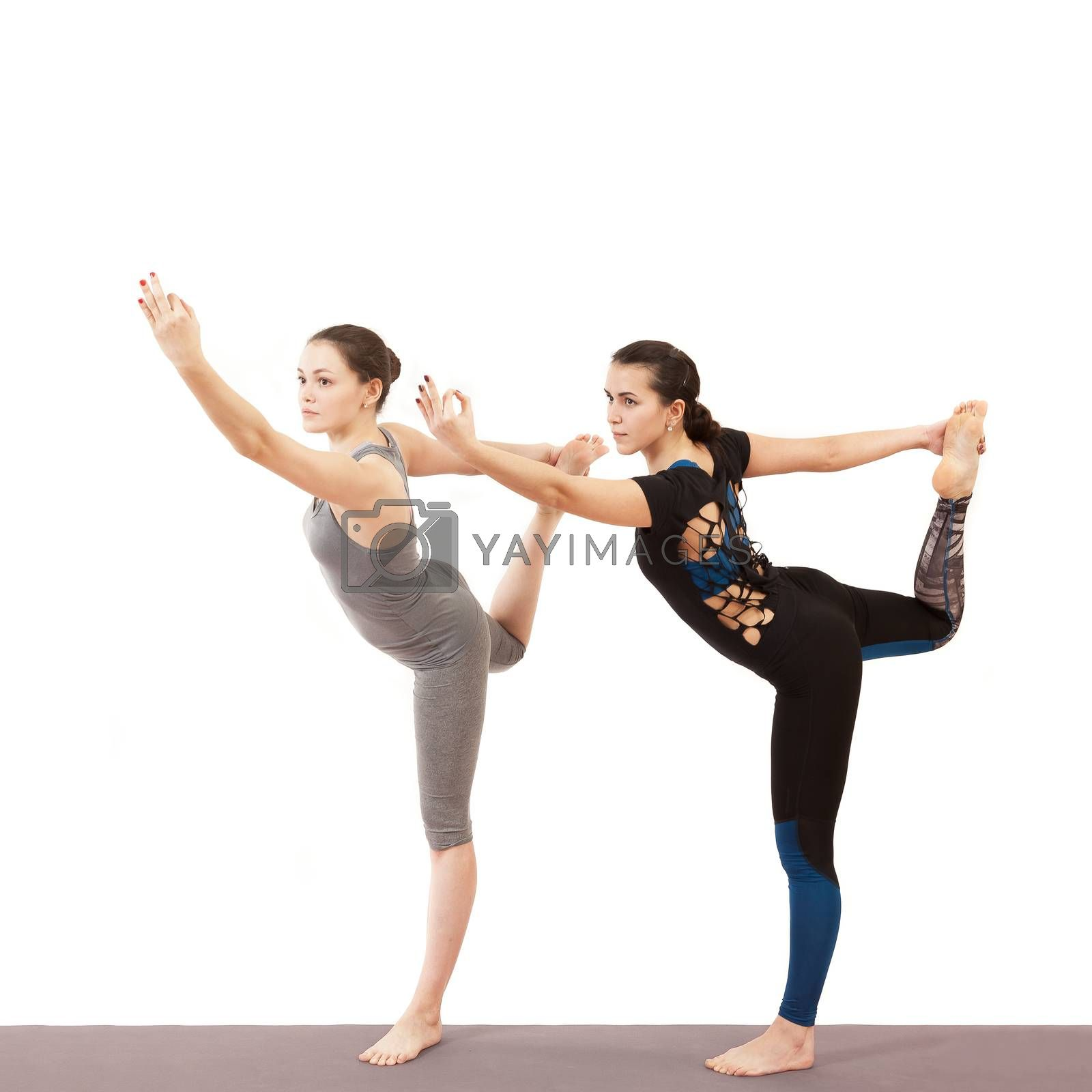 two young girls doing yoga on a white background
