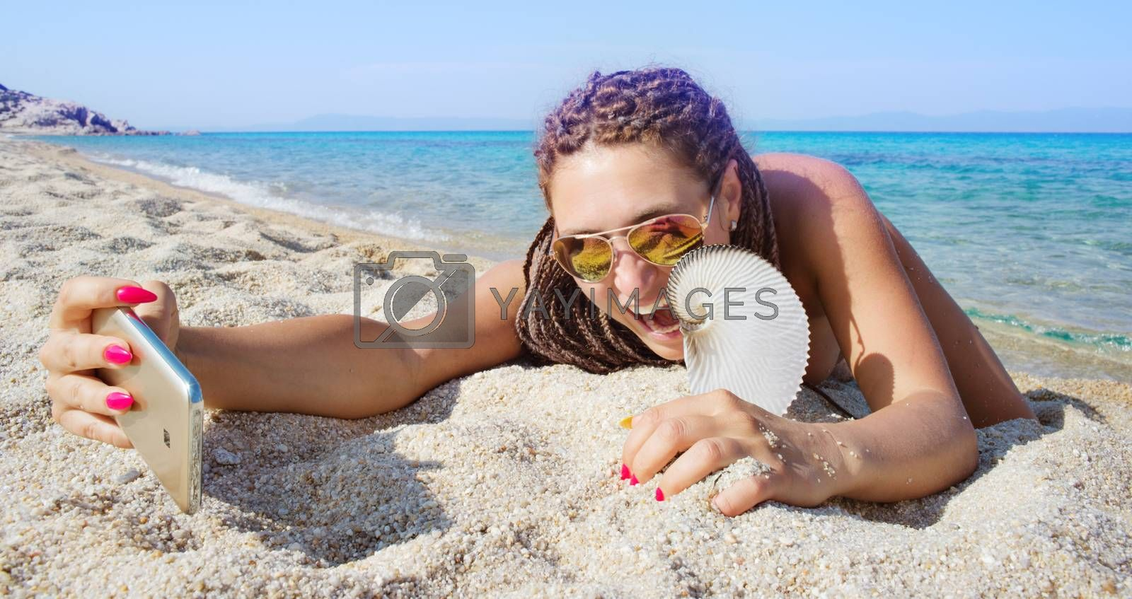 Gorgeous female is making selfie with smartphone lying on a sandy beach of a beautiful distant sea shore, holding nautilus shell.