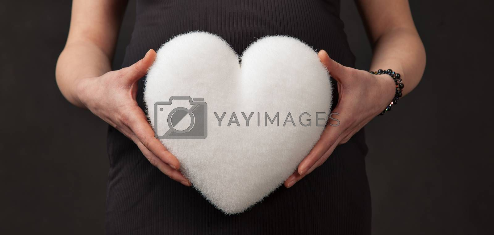 Hands of pregnant woman hold a white heart in front of her abdomen.