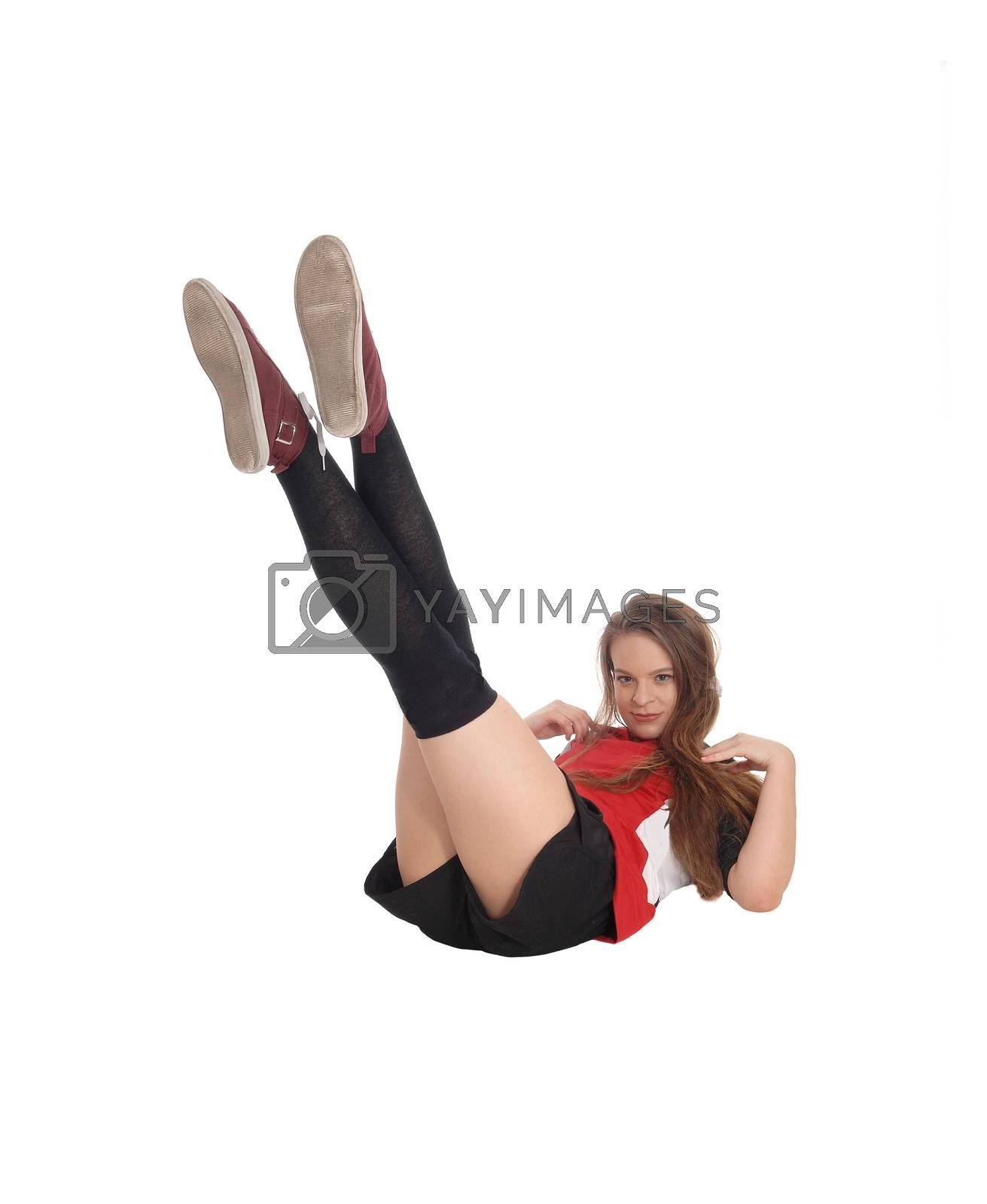 A young slim woman lying on the floor in the studio lifting her legs up strait in the air, isolated for white background