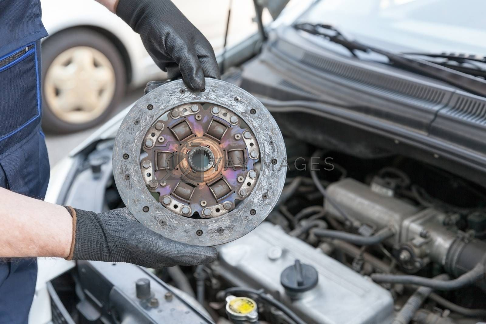 Auto mechanic wearing protective work gloves holds old clutch disc over  a car engine