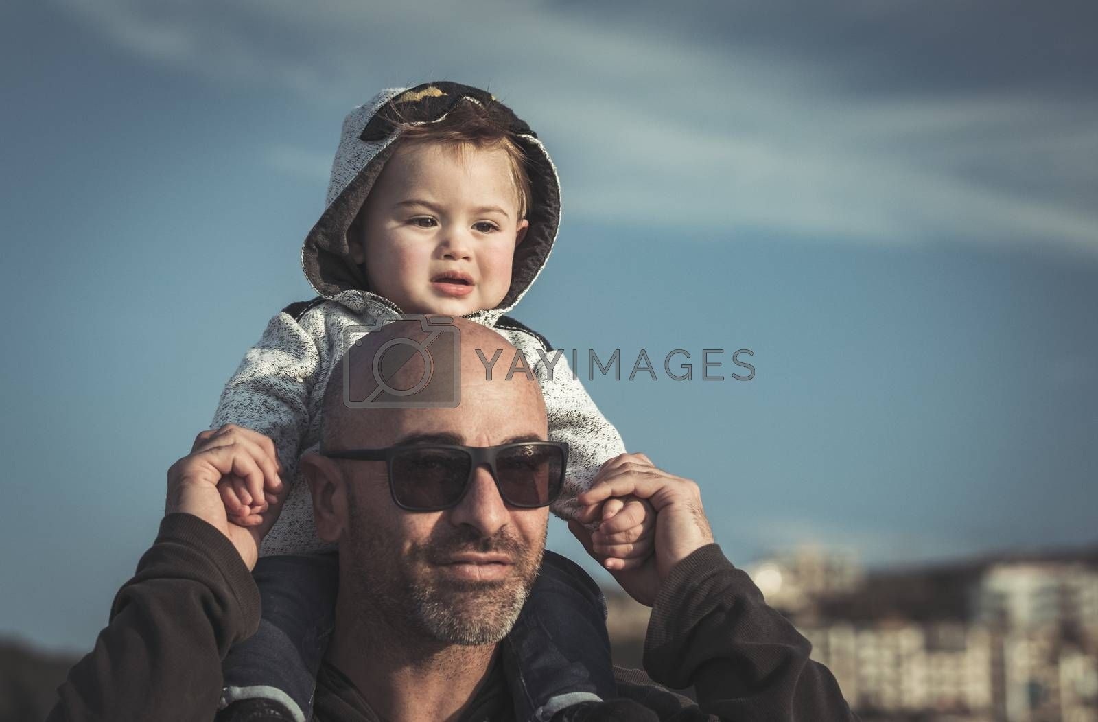 Portrait of a father carrying his cute little son on shoulders, baby and daddy with pleasure spending time together outdoors, happy family life