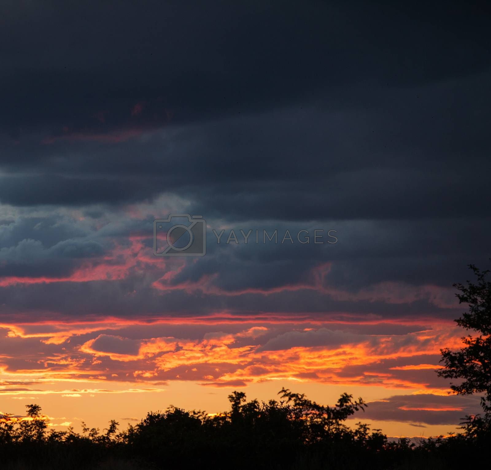 Dramatic clouds in orange, purple and black during sunset.