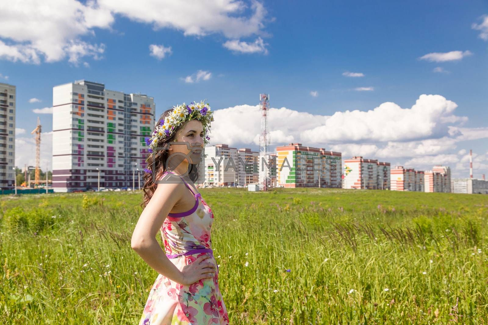Portrait of the beautiful girl in the field against the background of the city