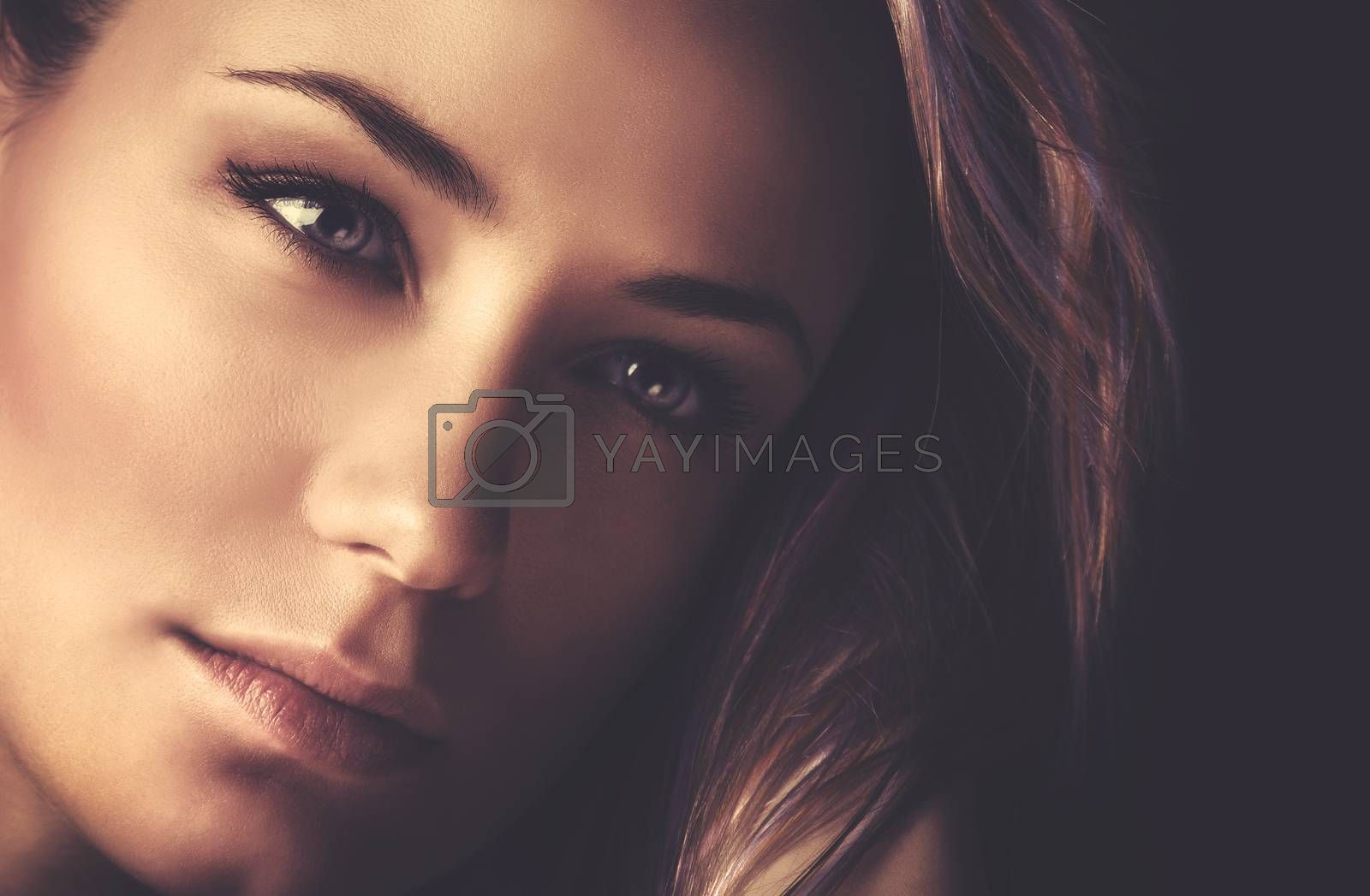 Closeup portrait of a beautiful woman with perfect nude makeup on dark background, gorgeous photoshoot of attractive model