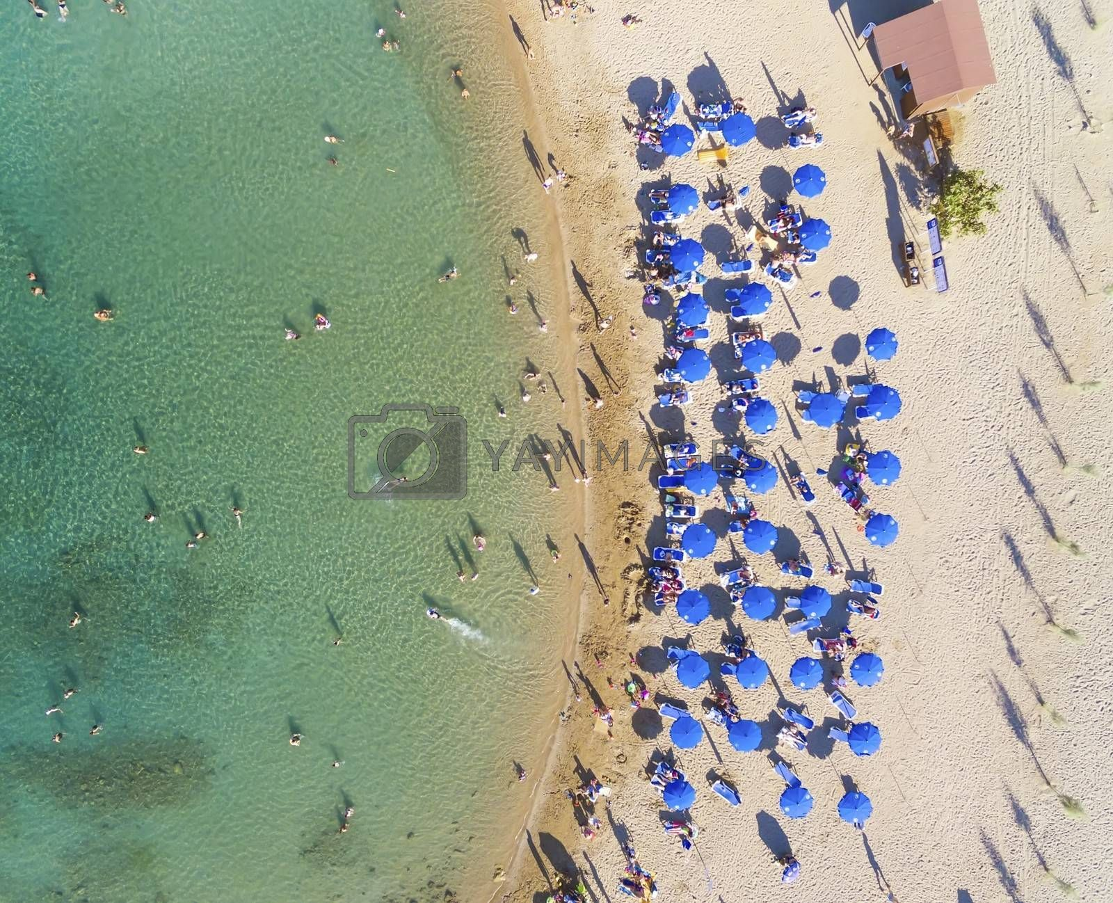 Aerial bird's eye view of sandy beach in Protaras, Famagusta, Cyprus island at the Agia Triada bay. Sun umbrellas, sea beds and silhouette of people sunbathing and swimming during the summer holiday heat