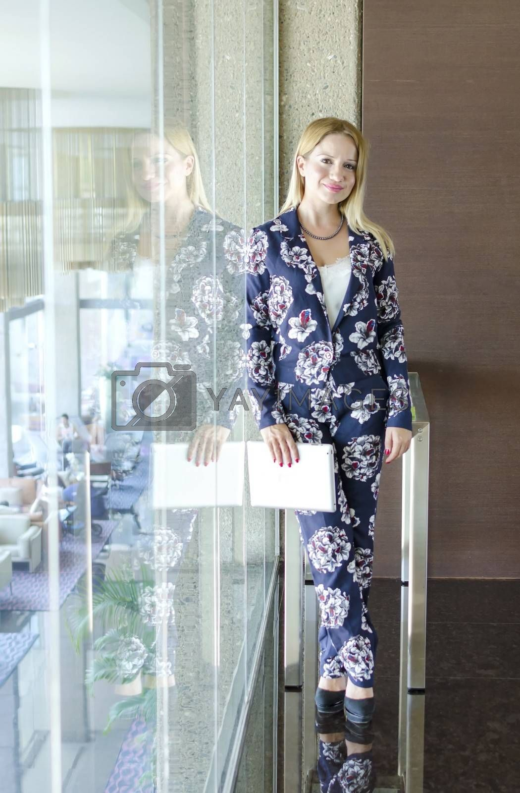 One modern beautiful young blonde white caucasian professional business woman smiling, looking confident, holding a tablet, wearing a work office blazer, standing in a conference meeting room alone with big windows on background.