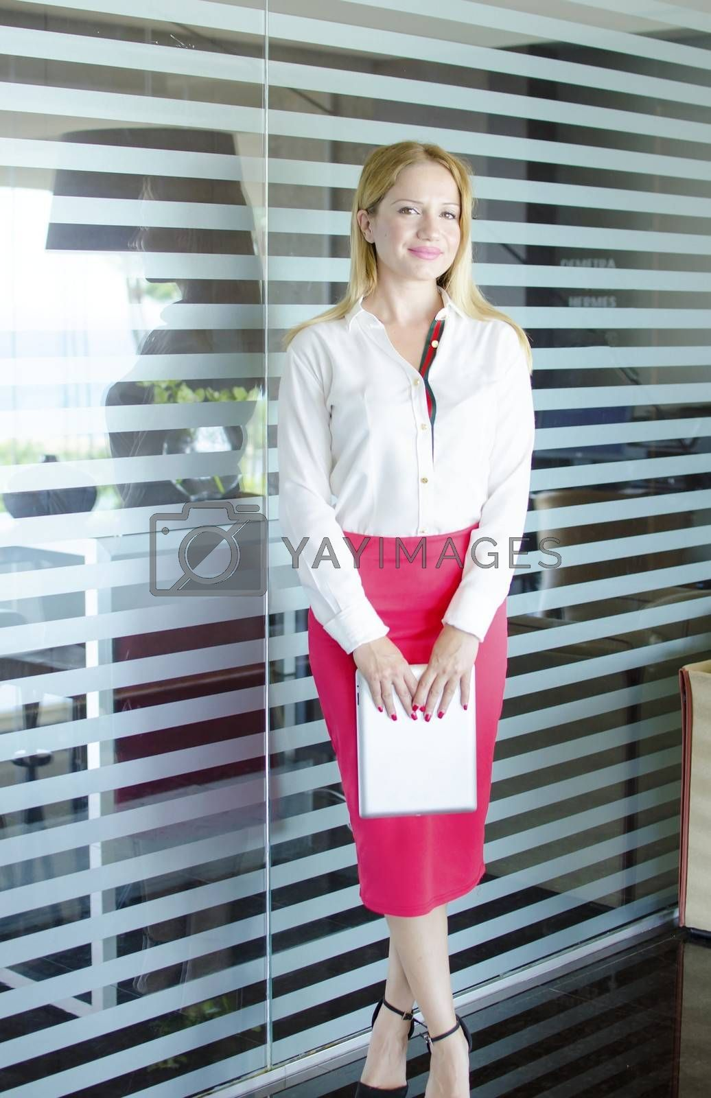 One modern beautiful young blonde white caucasian professional business woman smiling, looking confident, holding a tablet, wearing a work office white shirt and red pencil skirt, standing in a conference meeting room alone with big windows on background.