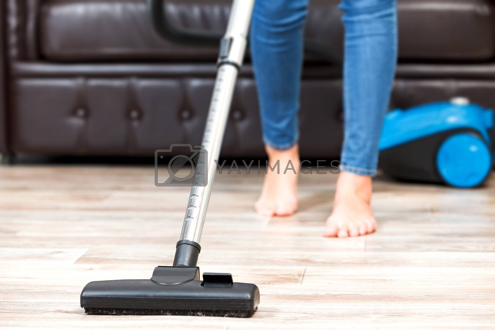 Young woman vacuum cleaning the apartment, housework