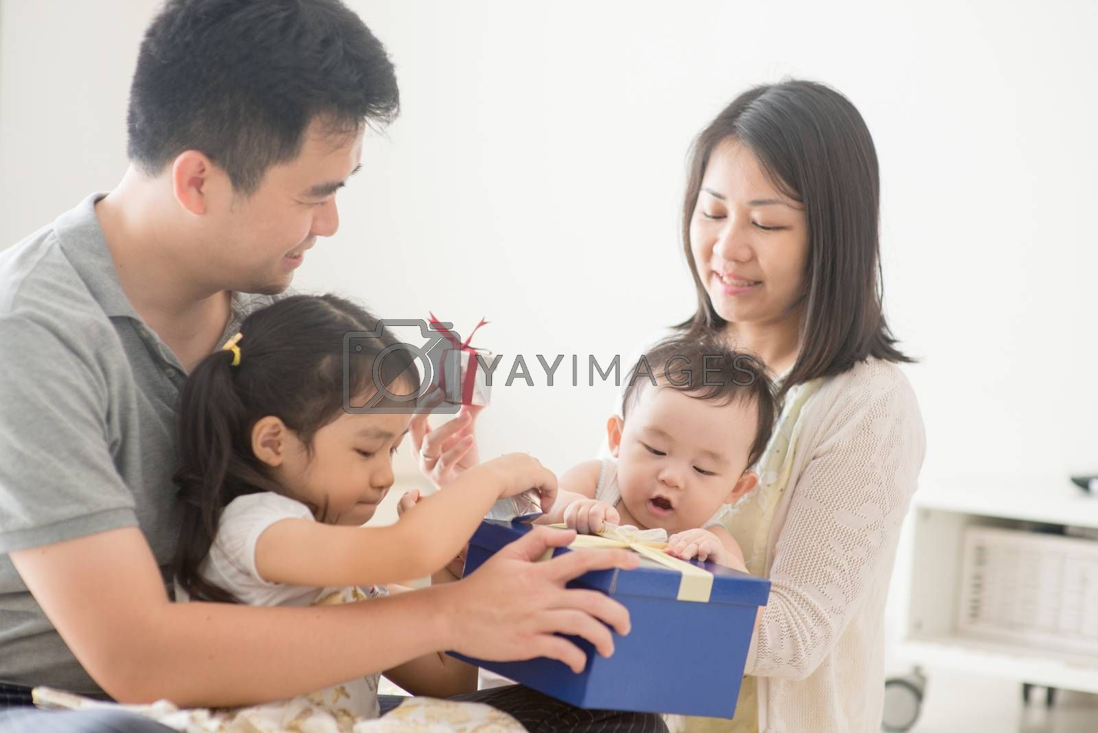 Parents and children boxing together. Asian family spending quality time at home, natural living lifestyle indoors.