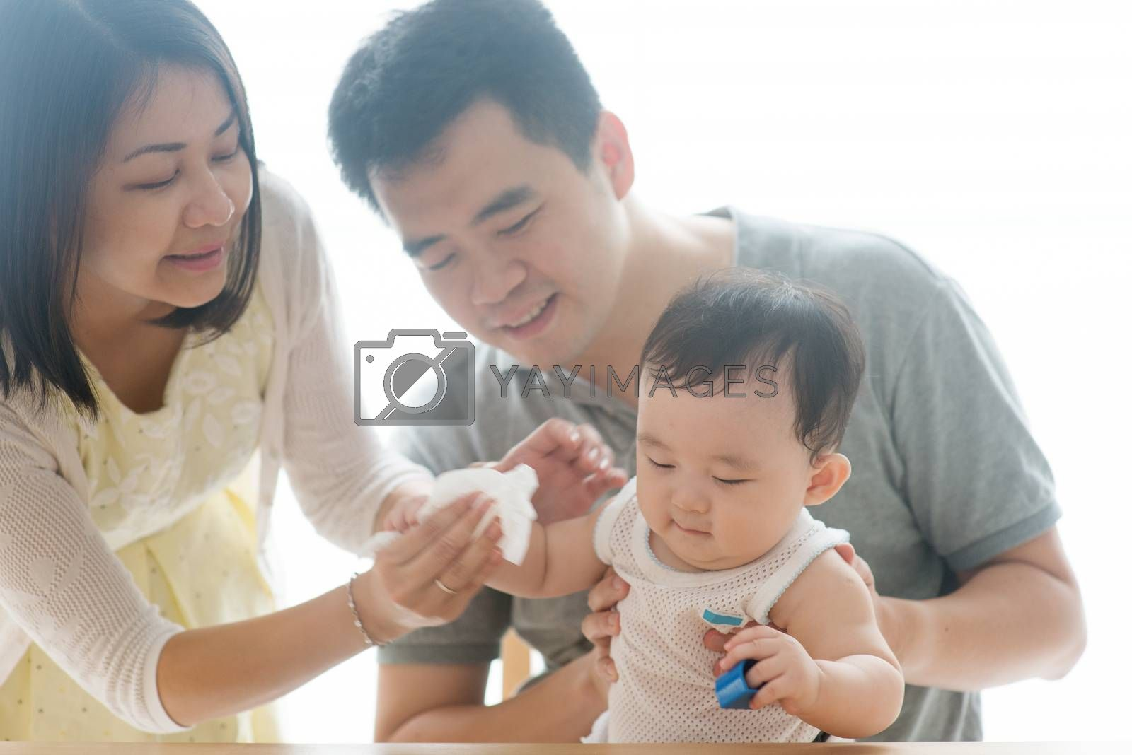 Mother wipes baby hand with tissue paper. Asian family spending quality time at home, living lifestyle indoors.