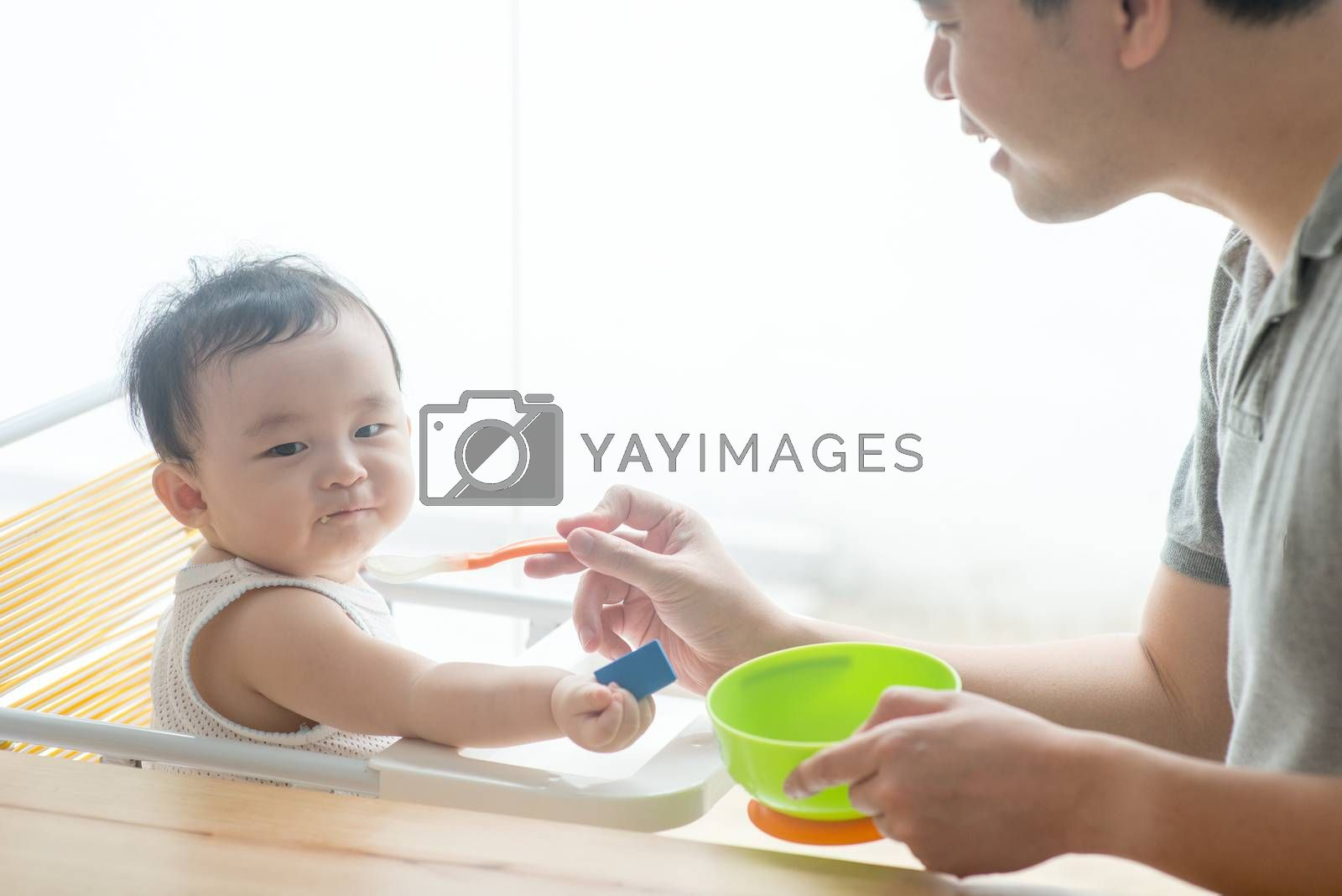 Happy Asian family at home. Father feeding solid food to his 9 months old child in the kitchen, living lifestyle indoors.