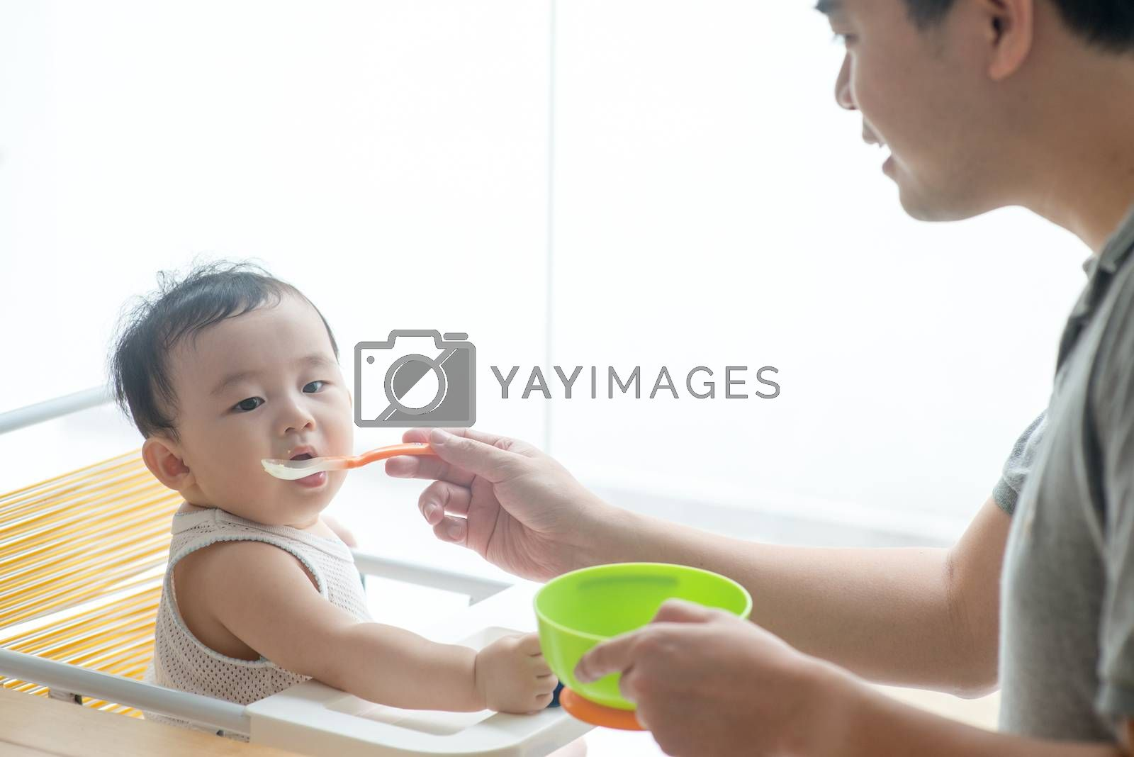 Happy Asian family at home. Father feeding solid food to his 9 months old baby boy in the kitchen, living lifestyle indoors.