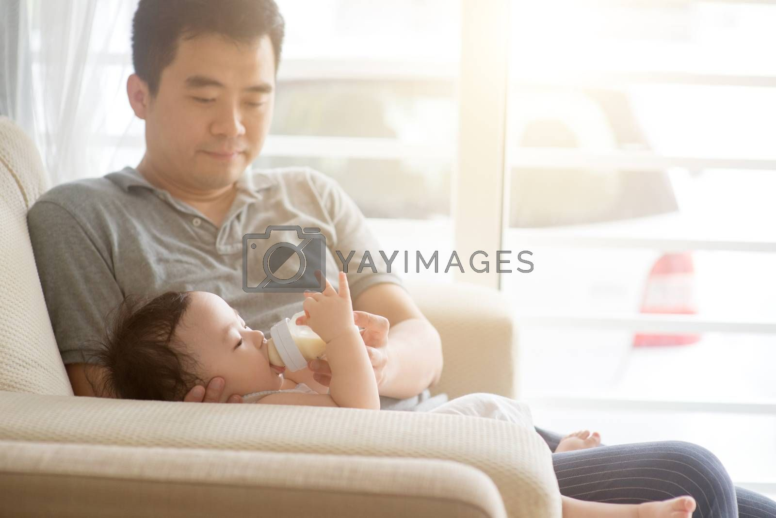 Happy Asian family at home. Father bottle feed formula milk to 9 months old baby boy, living lifestyle indoors.