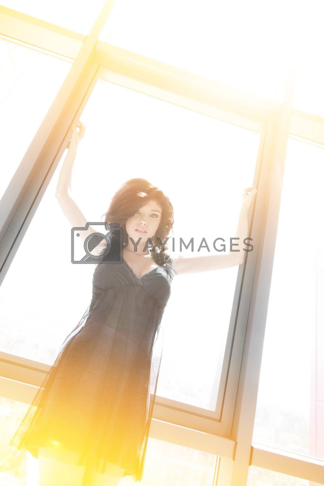 Young beautiful woman is stretching her arms on the window