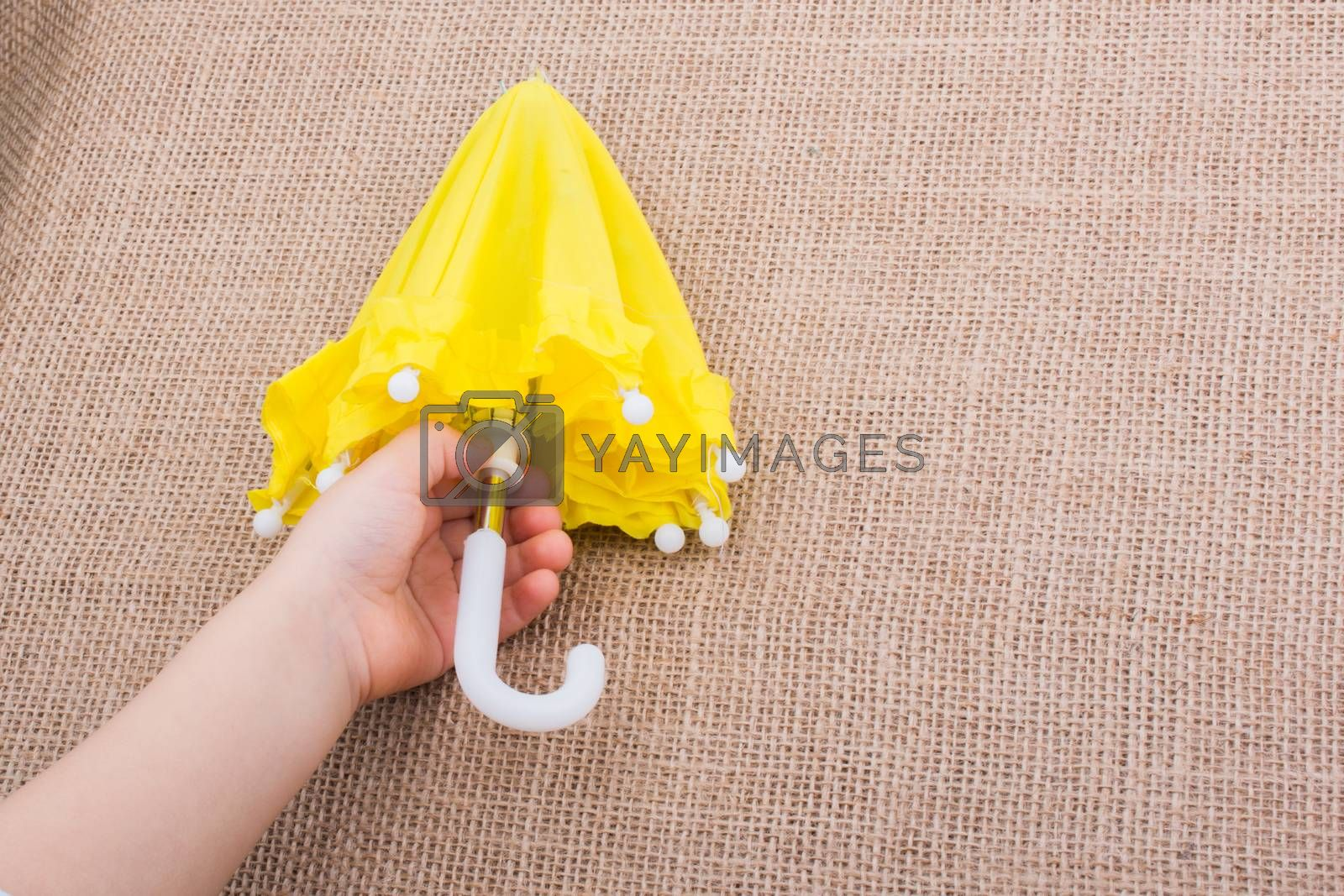 Yellow umbrella in a toddlers hand on canvas