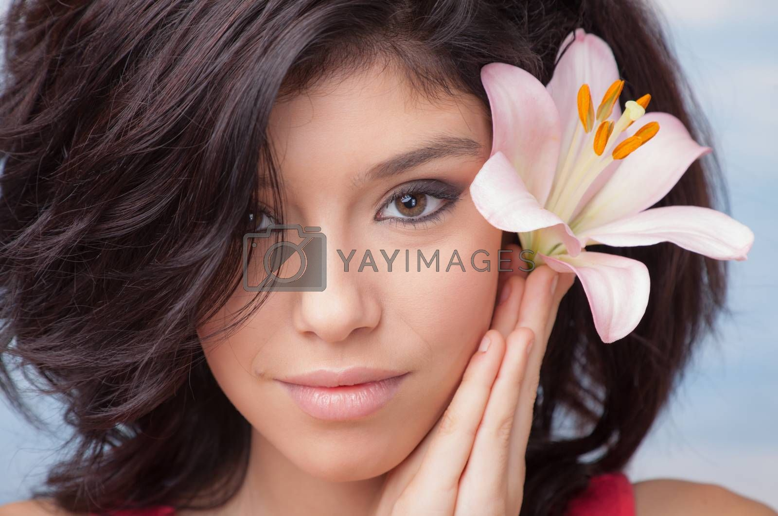 Portrait of a young beautiful girl with Lilium in her hair.