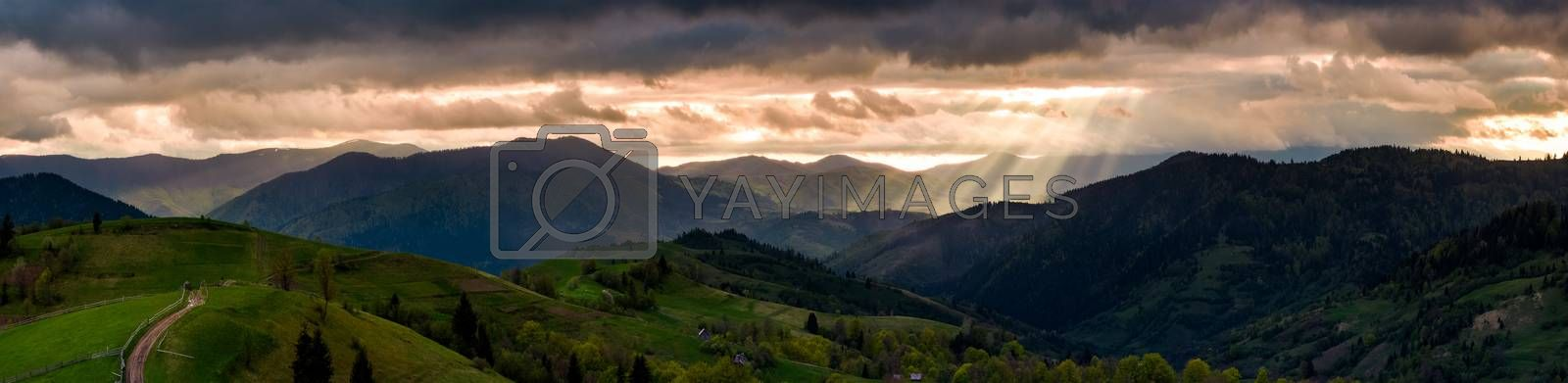 panorama of mountainous countryside at sunset. country road through rolling hills in to the distance. heavy clouds over the ridge. beams of lite from the heaven. beautiful and mysterious landscape