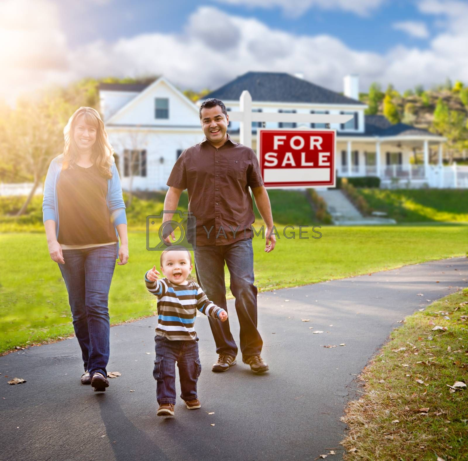 Happy Mixed Race Family Walking in Front of Home and For Sale Real Estate Sign.