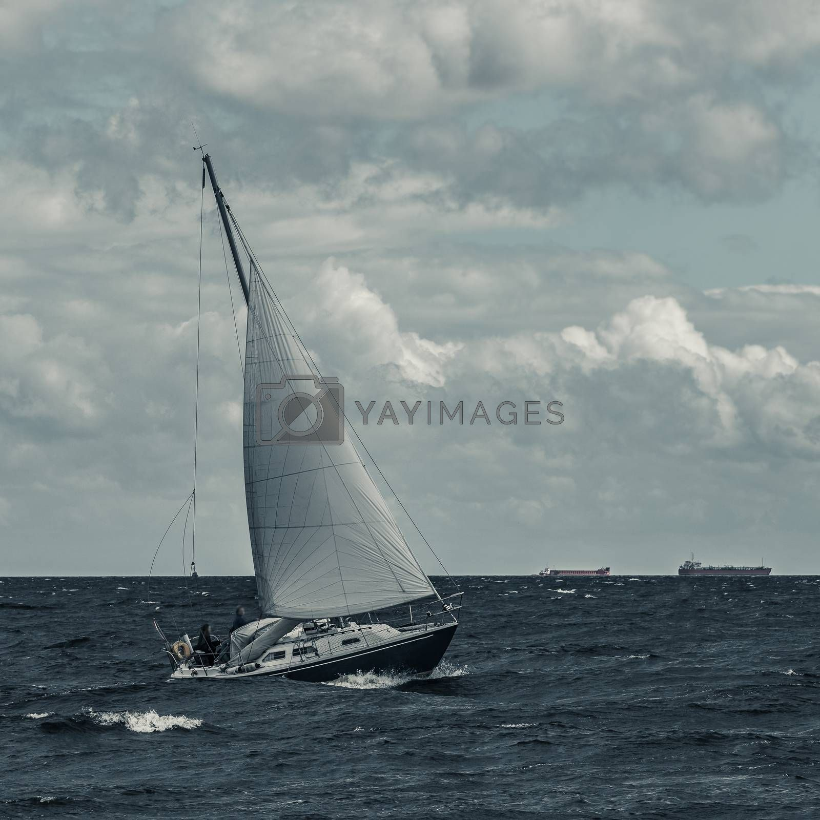Blue sailboat in a travel at stormy sea. Regata journey. Toned