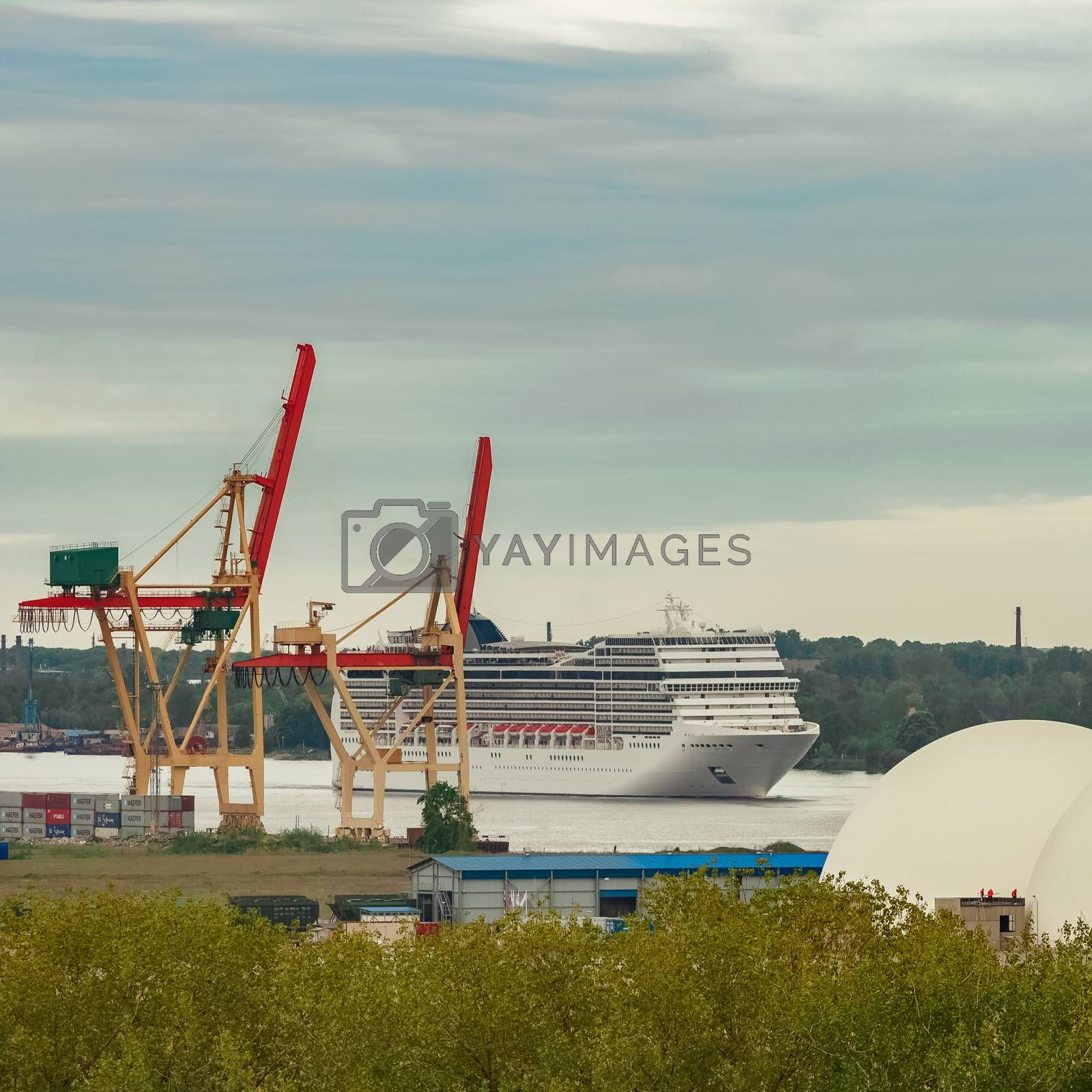 Big white cruise liner sailing past the cargo port