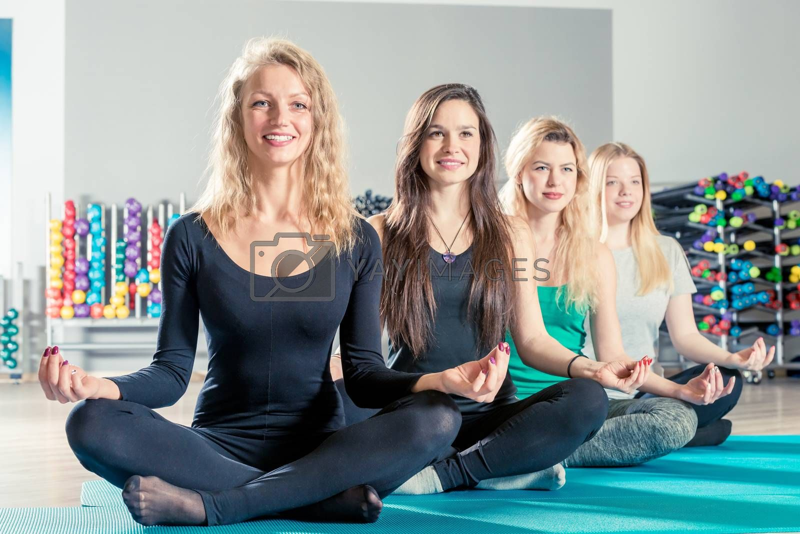 charming girls sit in a lotus position during a yoga training session in the gym