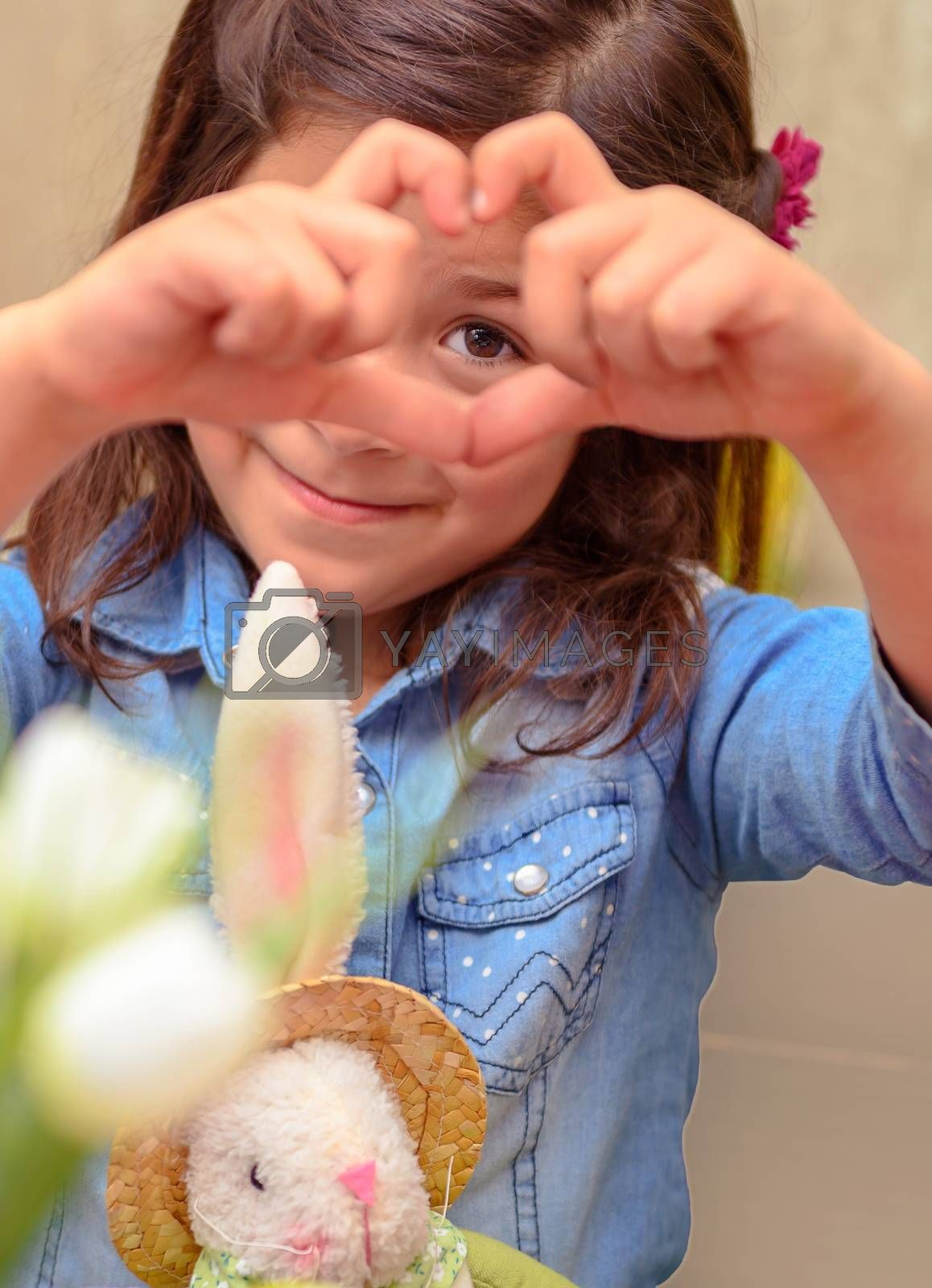 Portrait of a nice little girl shows gesture heart, spending time at home with her friend, little bunny soft toy, traditional symbol of Easter holiday, love concept