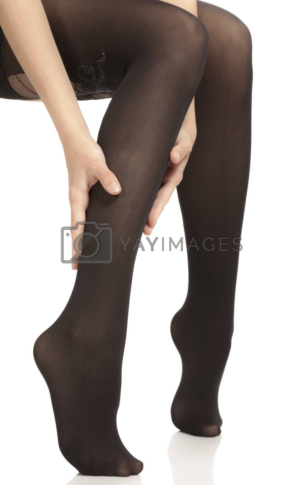 Close-up of female legs with pantyhose. Woman is rubbing her calf to relax pain.