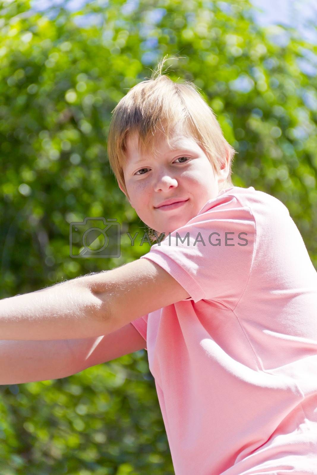 Smiling boy in pink shirt playing on stone wall