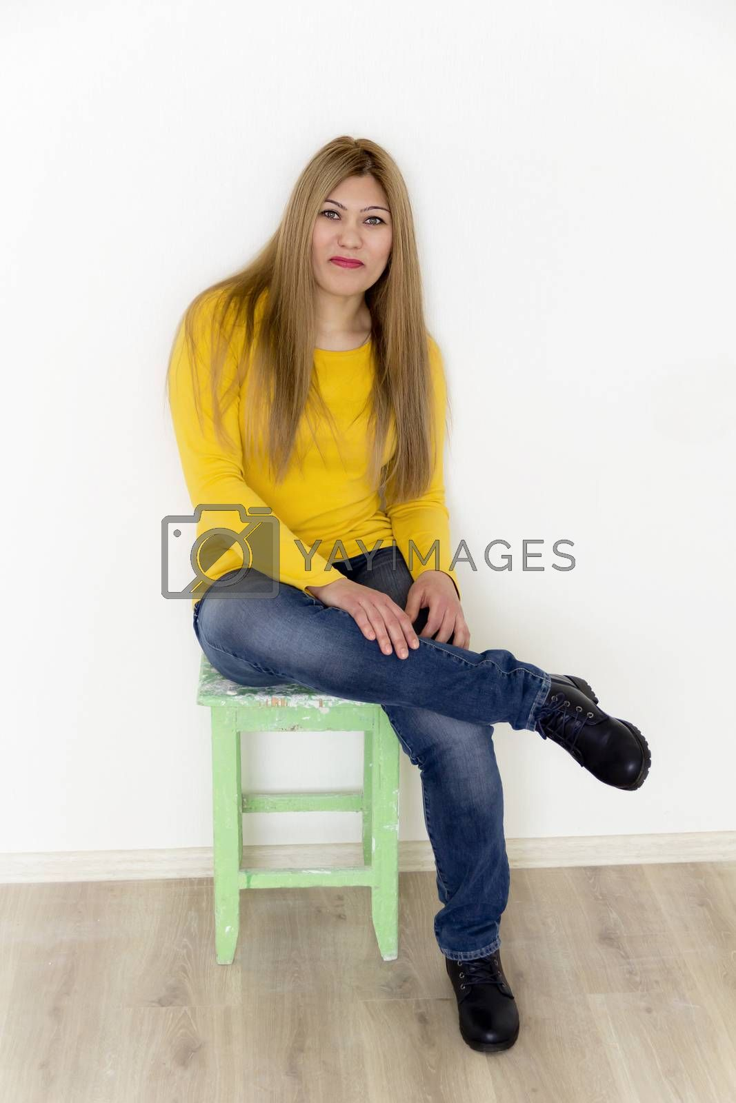 Attractive young girl with long straight hair near white wall