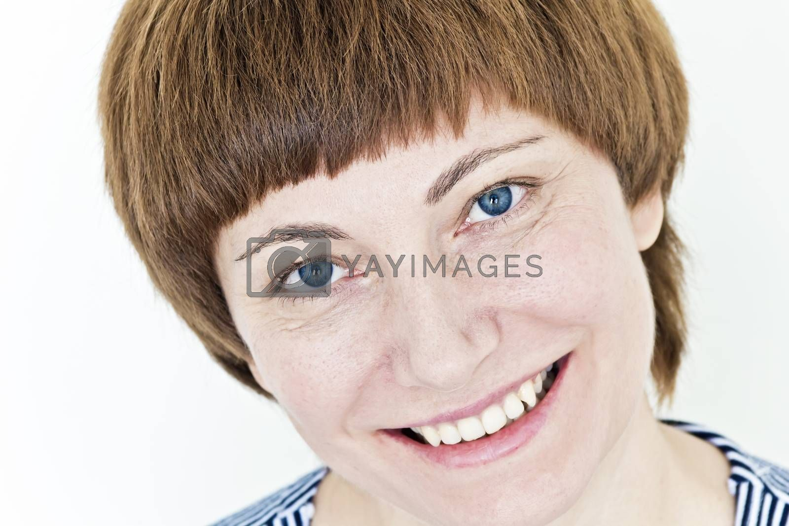 Smiling face of woman with red hair and blue eyes on white