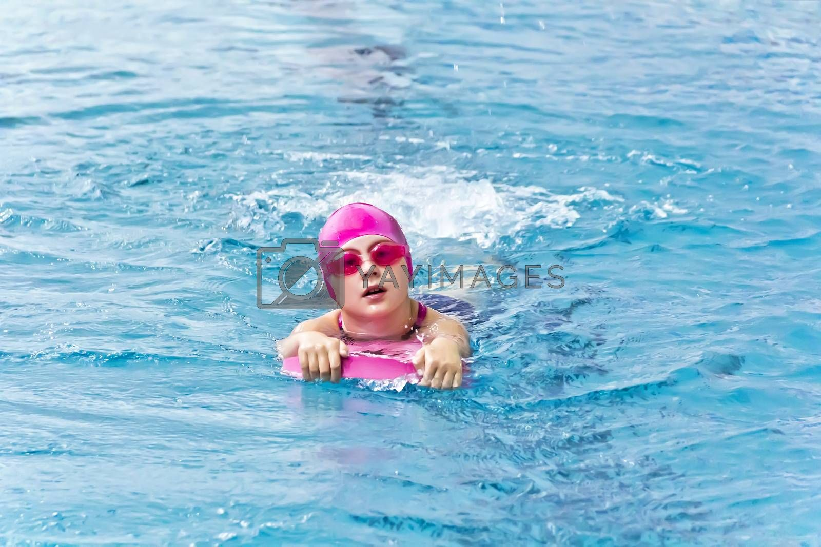 Cute girl with pink rubber hat are swimming in pool
