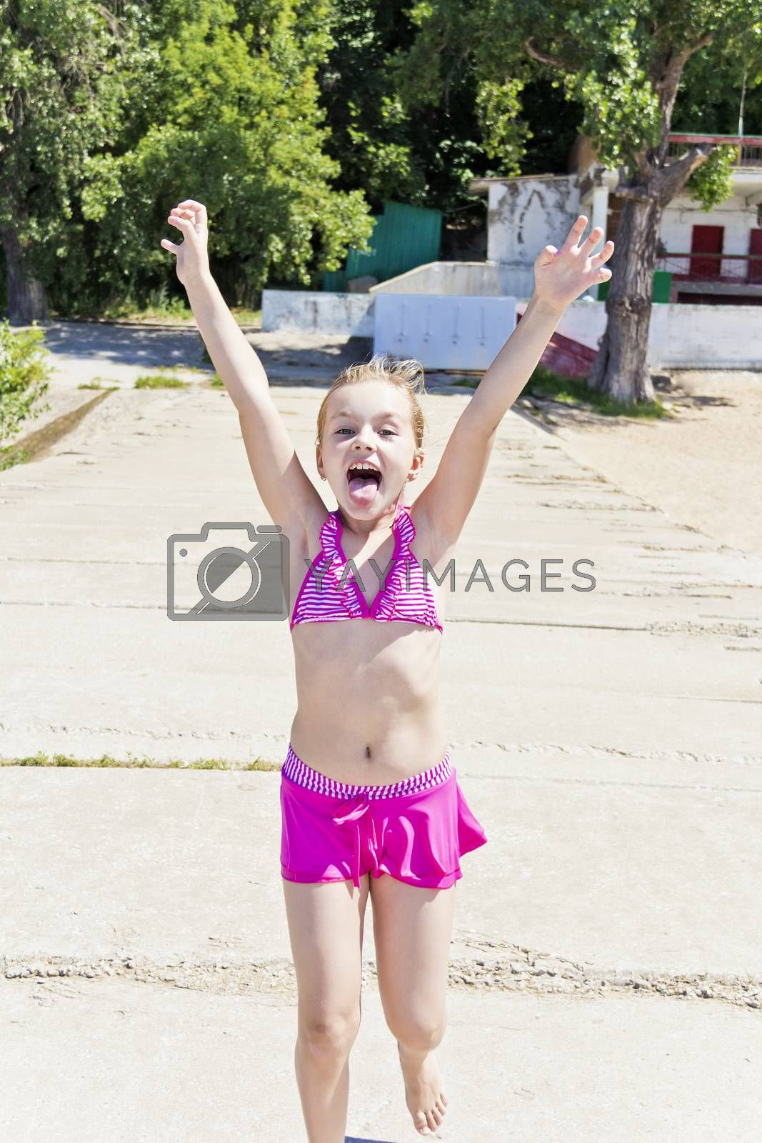 Running and screaming girl on the riverbank in pink swimsuit