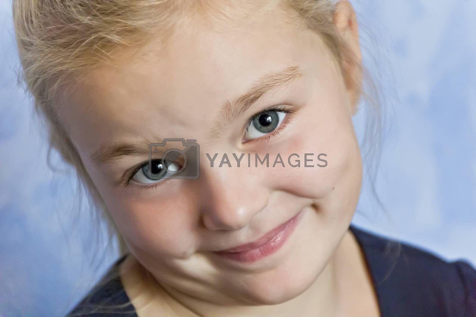 Cute smiling girl with blond hair on blue background