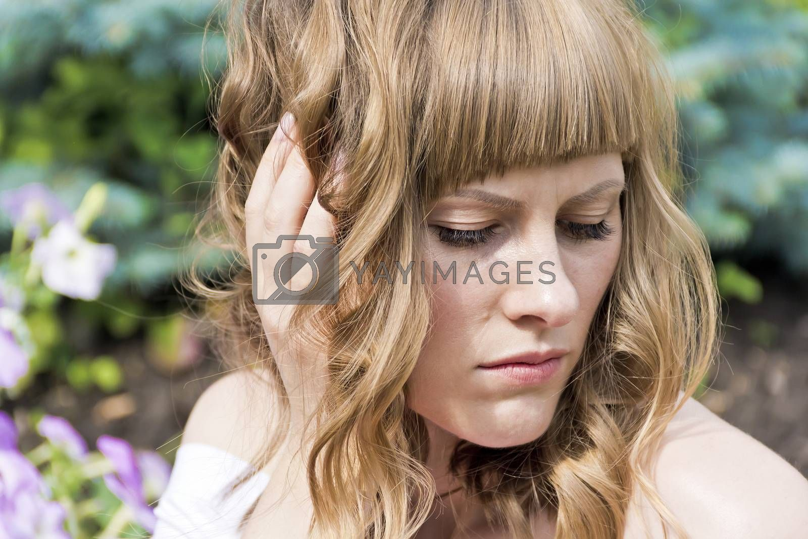 Horizontal portrait of youngl woman with blond hair on summer background