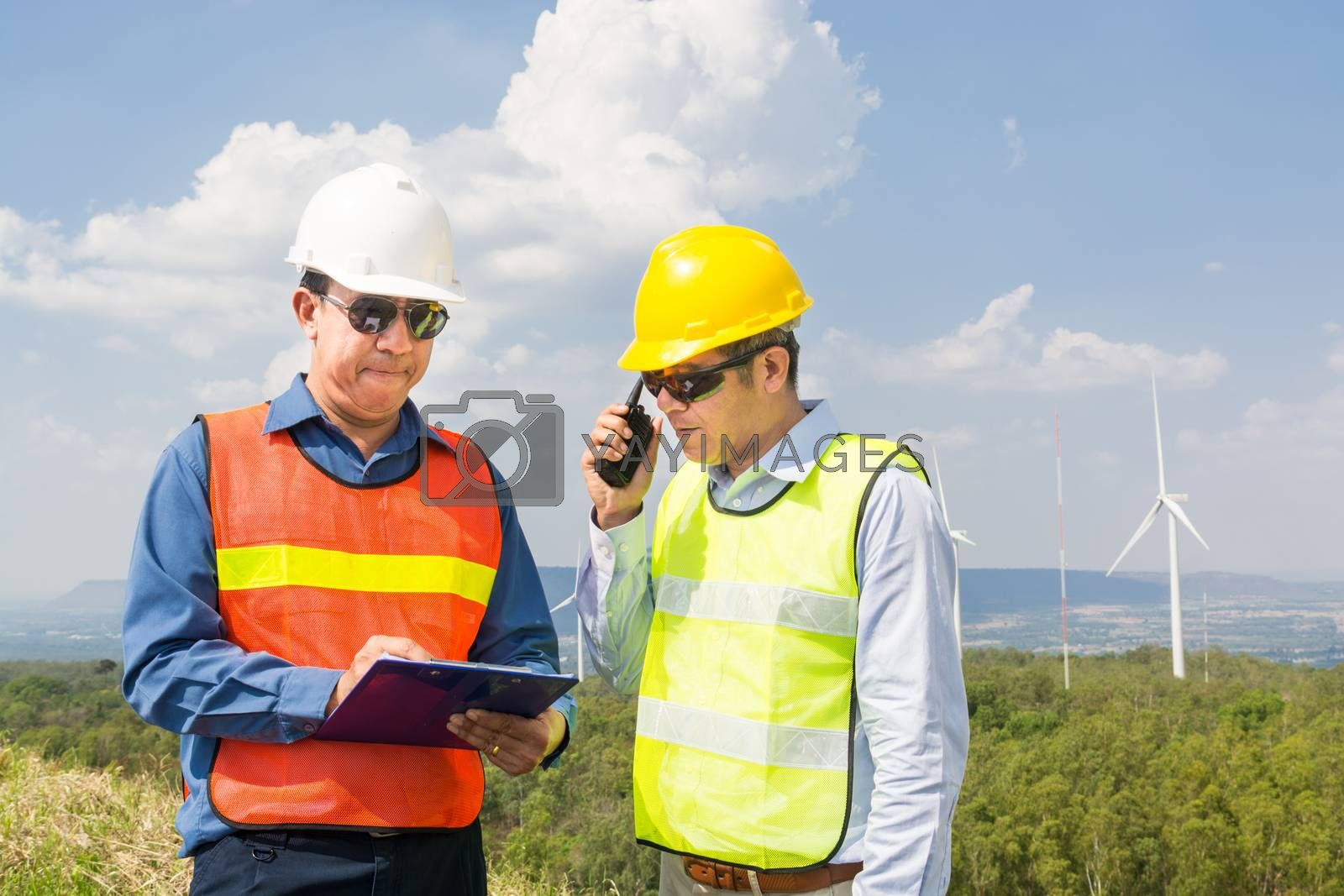 Male Engineer and Architect working Together with Hand-Held Transceiver Radio and Clipboard at Wind Turbine Power Generator Field as infrastructure construction Project Development Teamwork