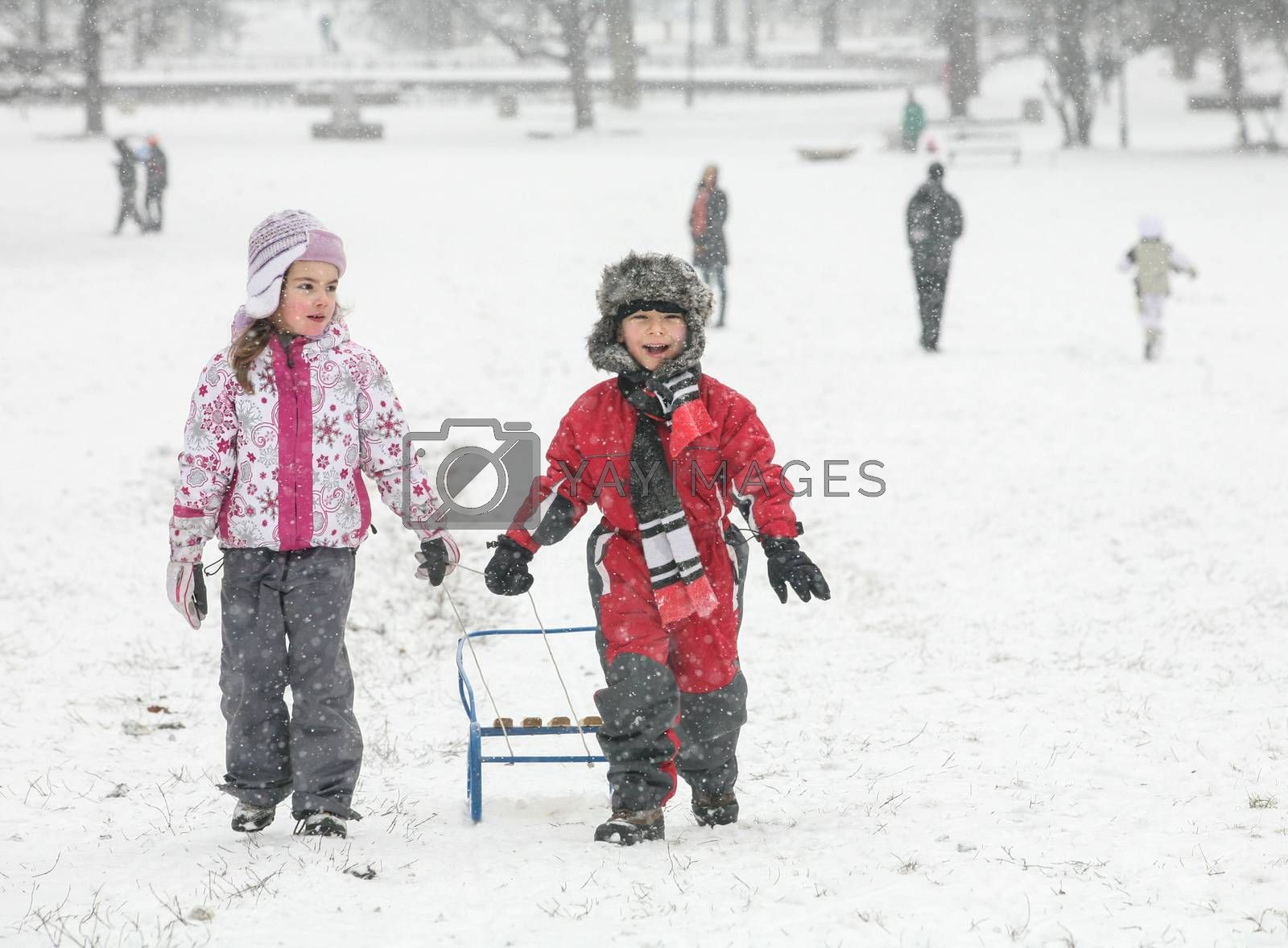 Two happy kids are pulling a sled in the snow during a cold winter day.
