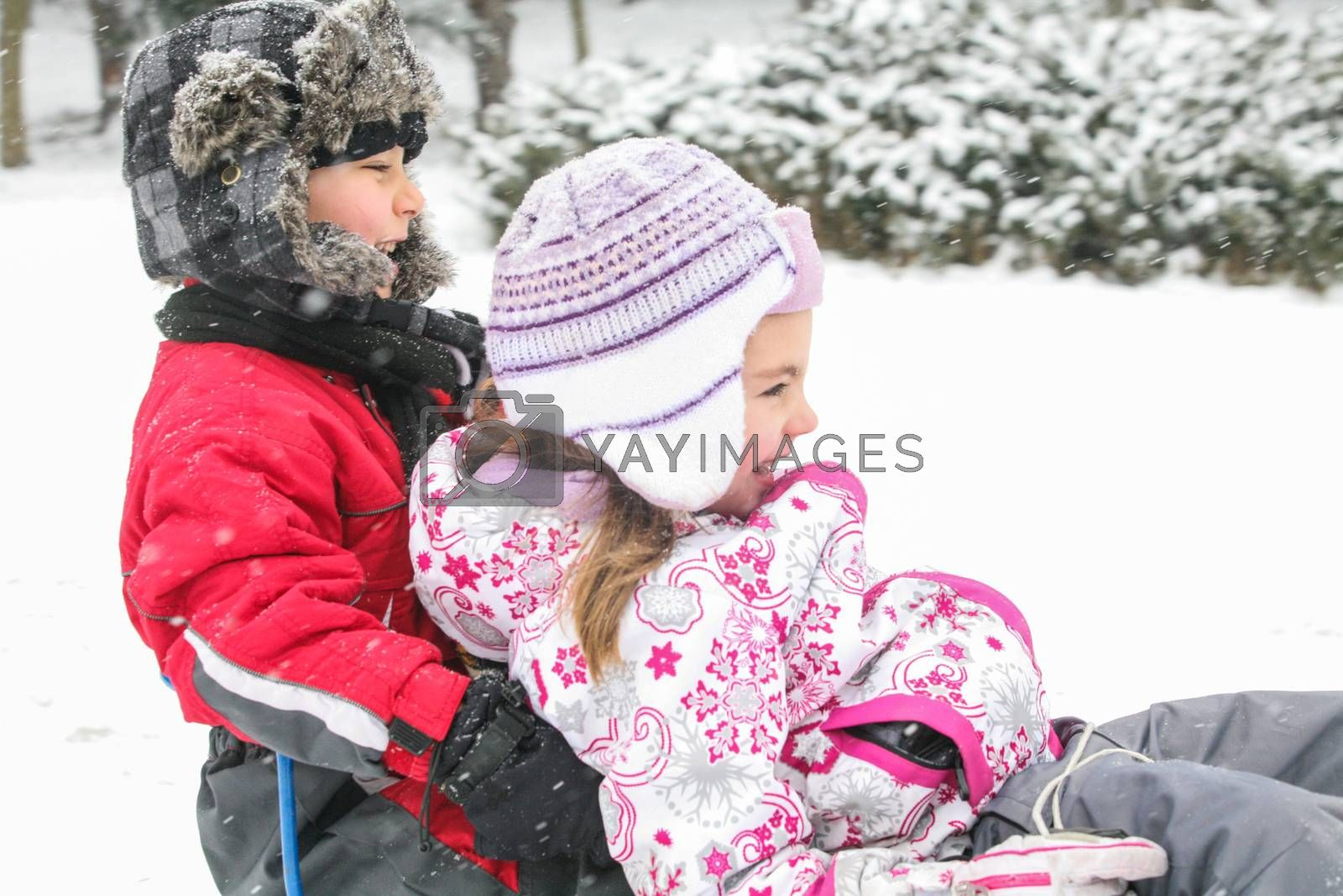 Two kids are playing in the snow on a cold winter day.