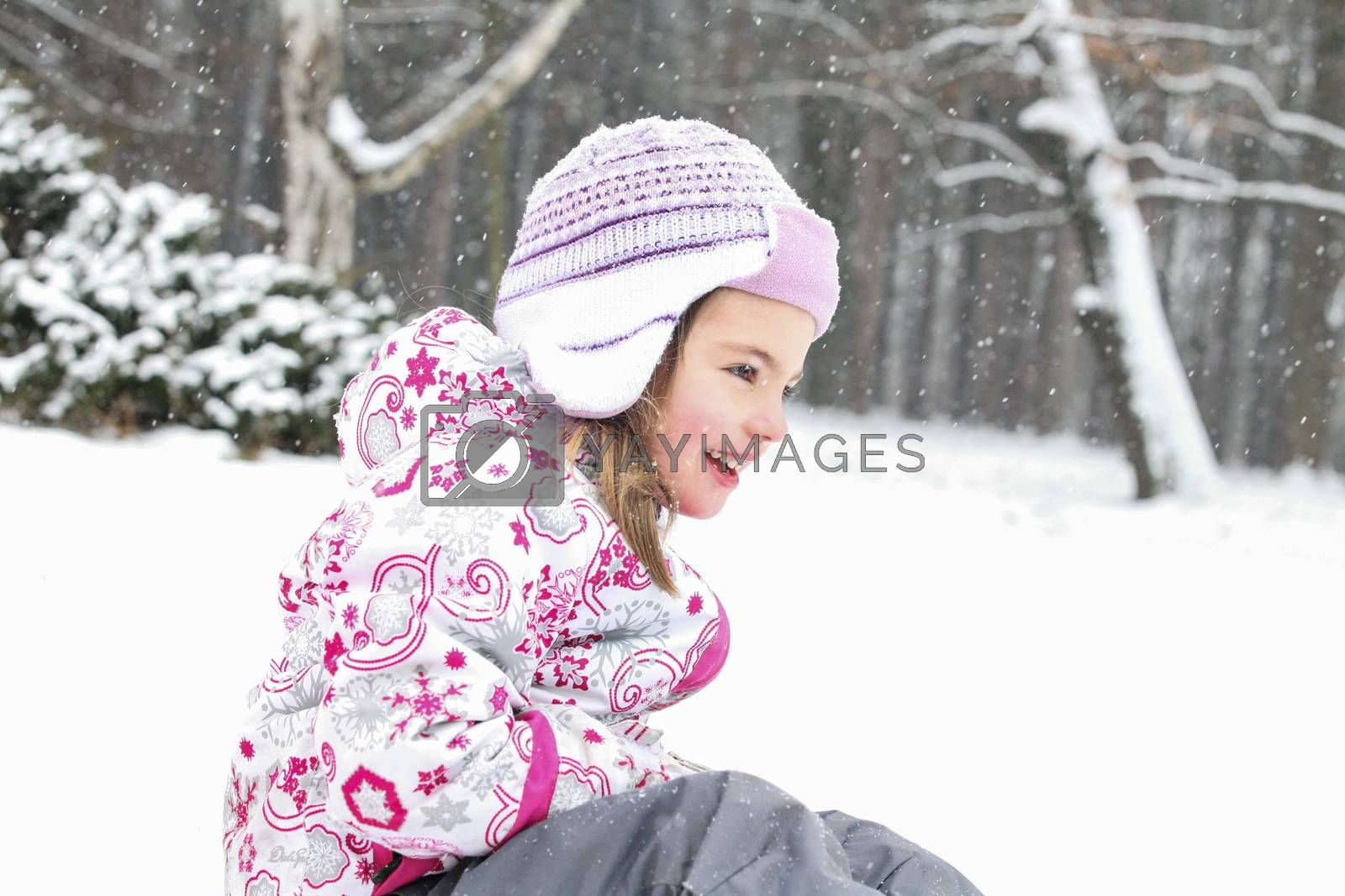 Happy smiling girl is playing on the snow in a cold winter day.
