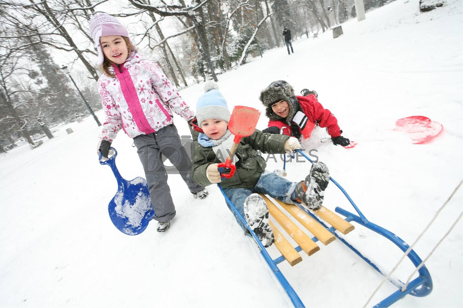 Three kids are playing with sleds in a cold winter day in the park.